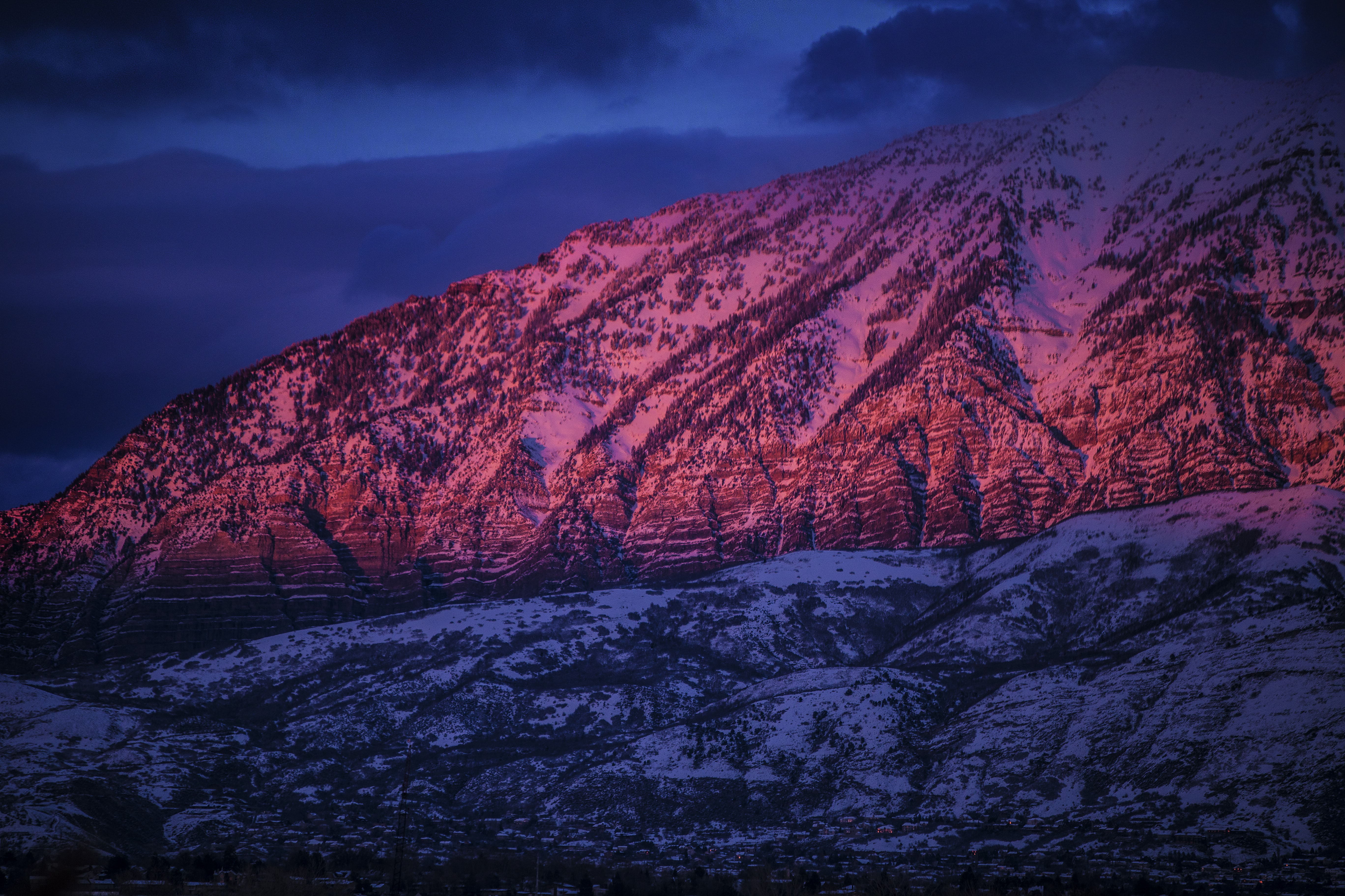 Red-hued sunlight falls on a snowy mountain slope in Provo during sunset