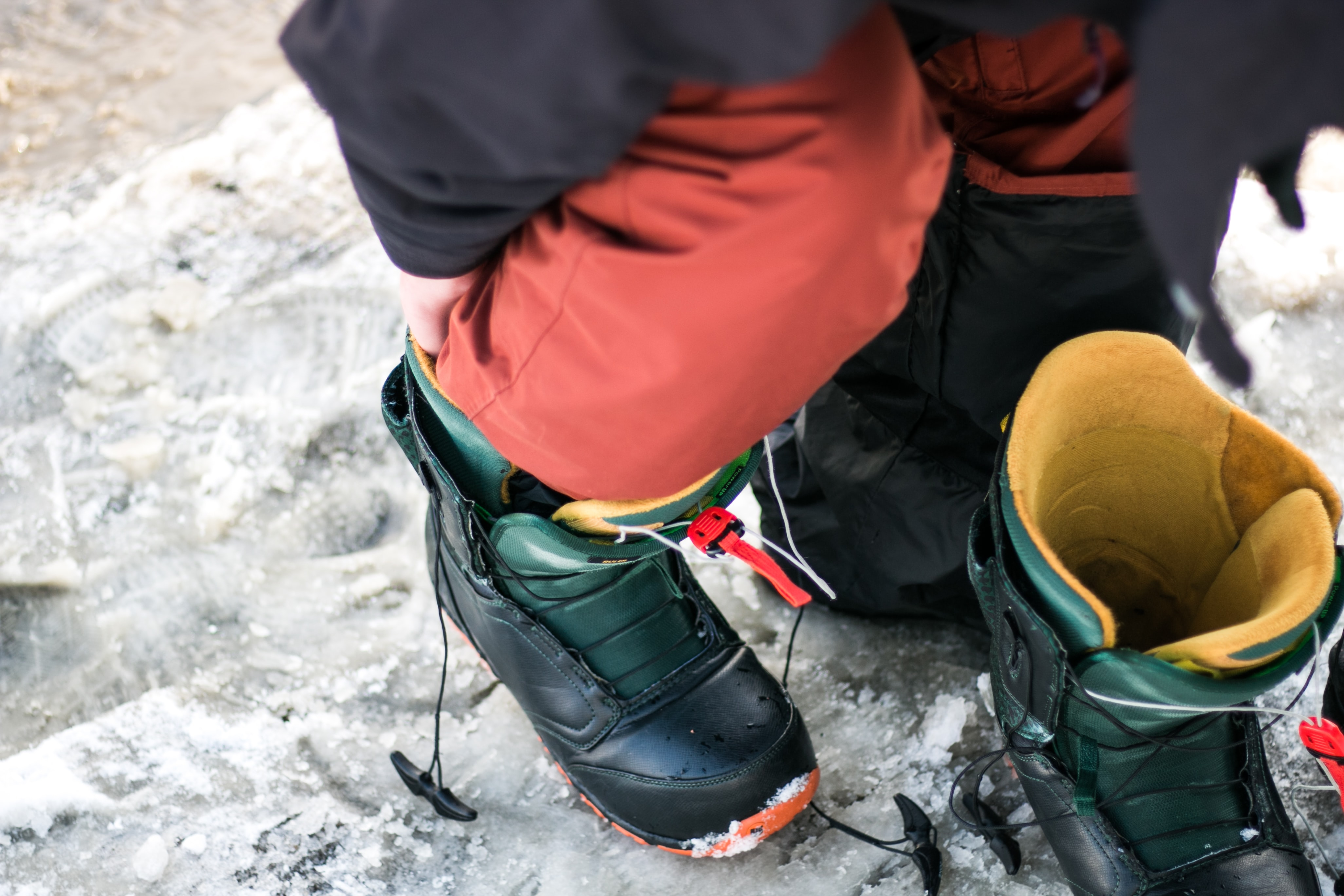 Hiker puts on hiking boots and gear before a trek through the snow