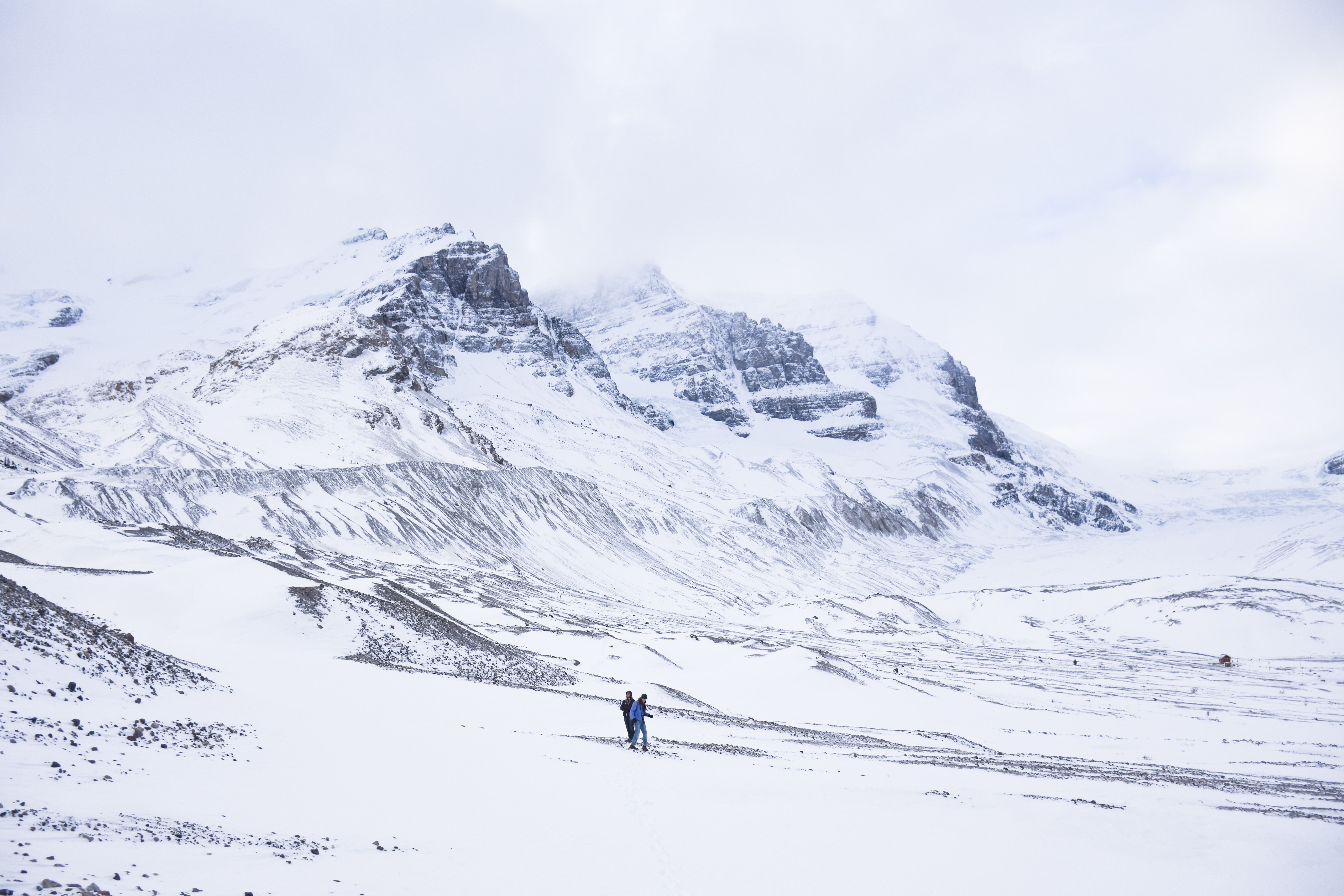 two person walking on snow covered ground next to mountains