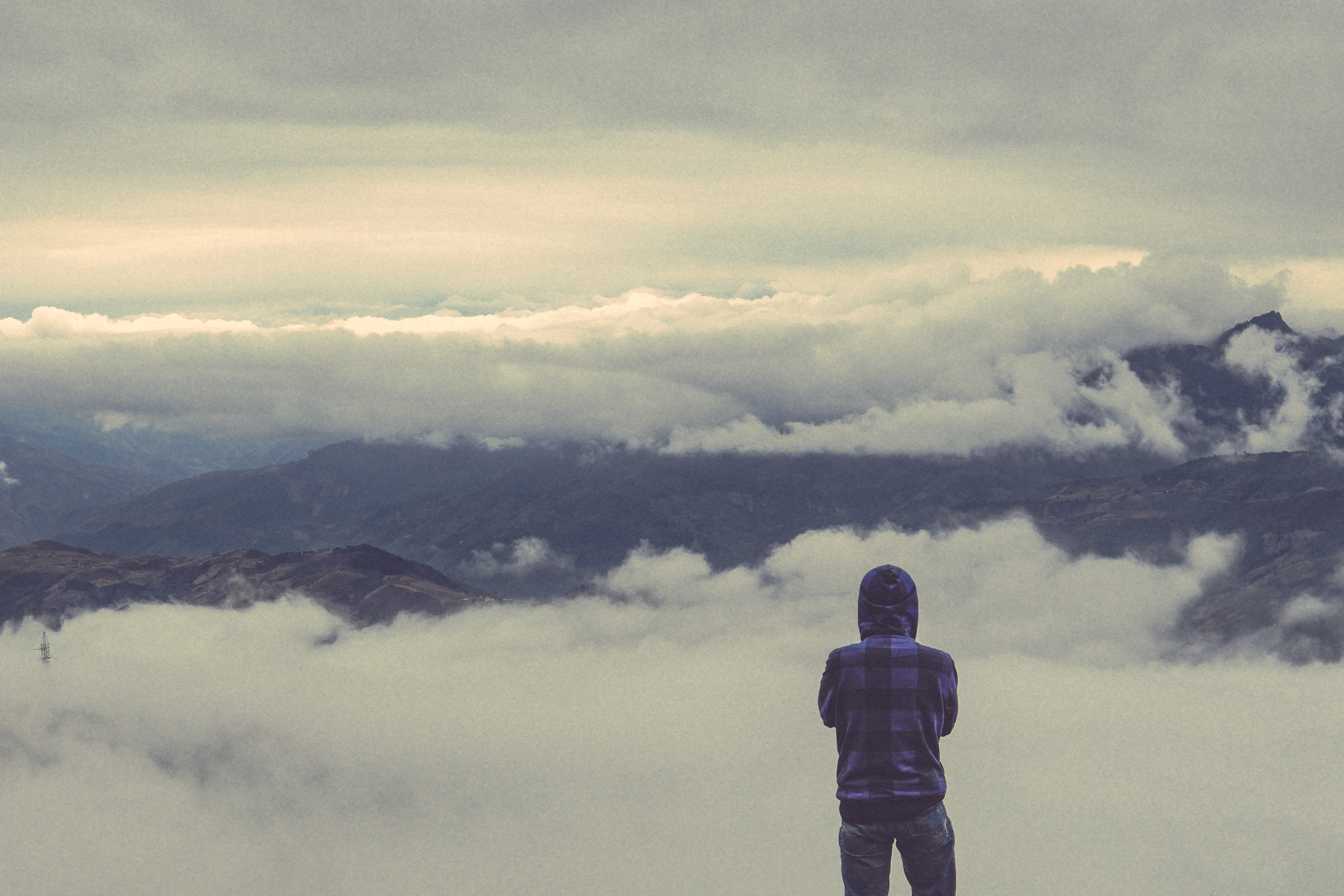 Hiker looks at foggy view of mountains in Tà Xùa