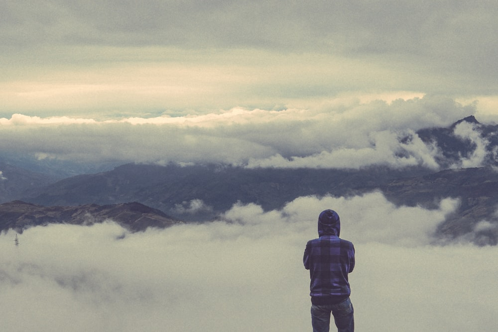 person looking at sea of clouds during daytime