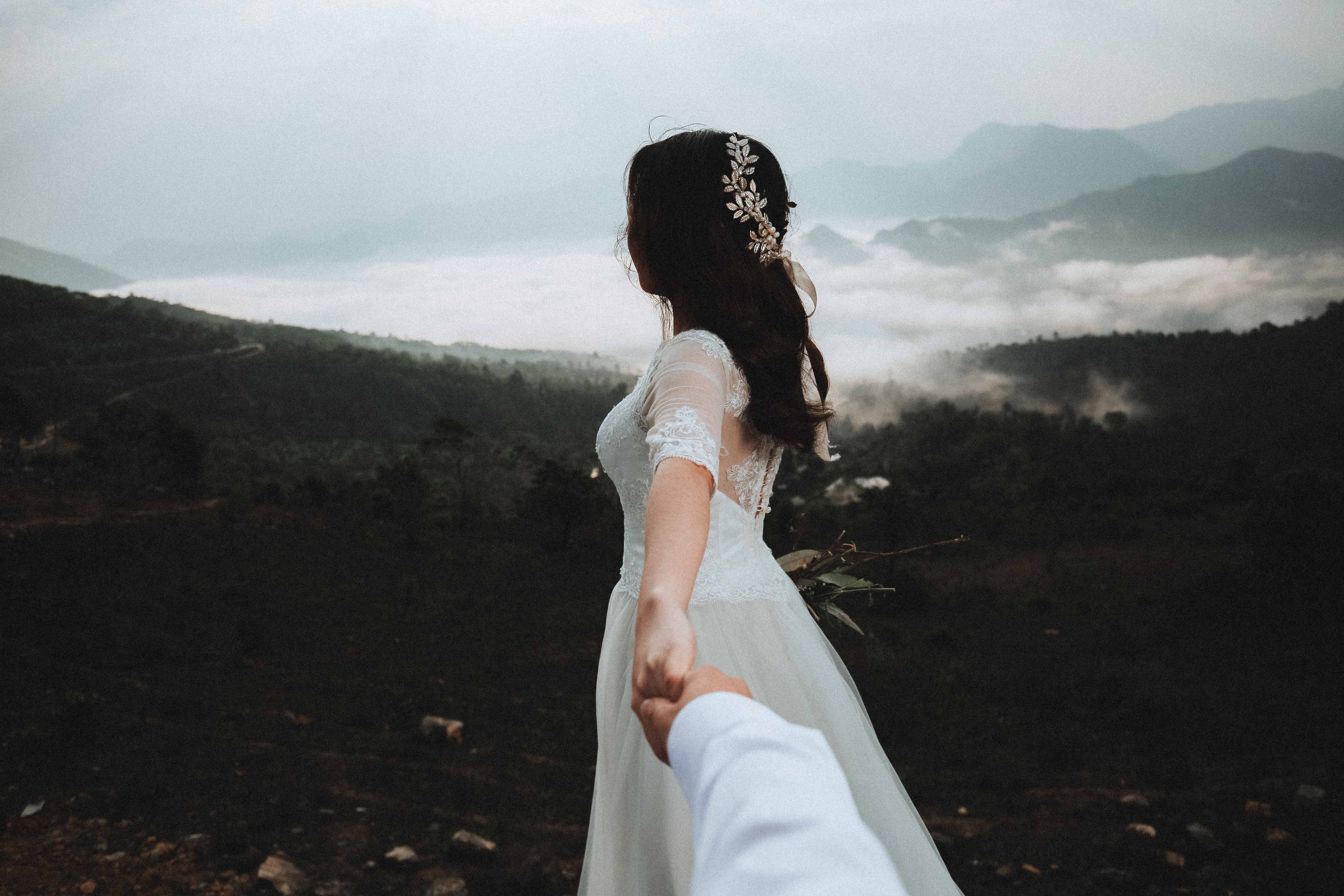 Groom reaches his arm out to beautiful bride on Vietnam mountain
