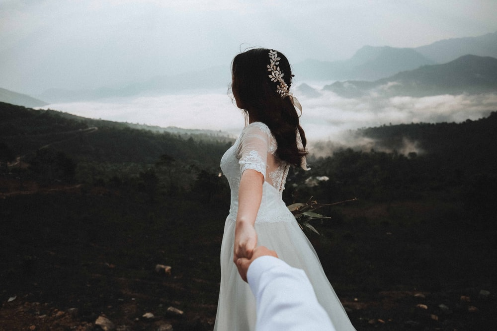 woman at the peak of the mountain holding hands