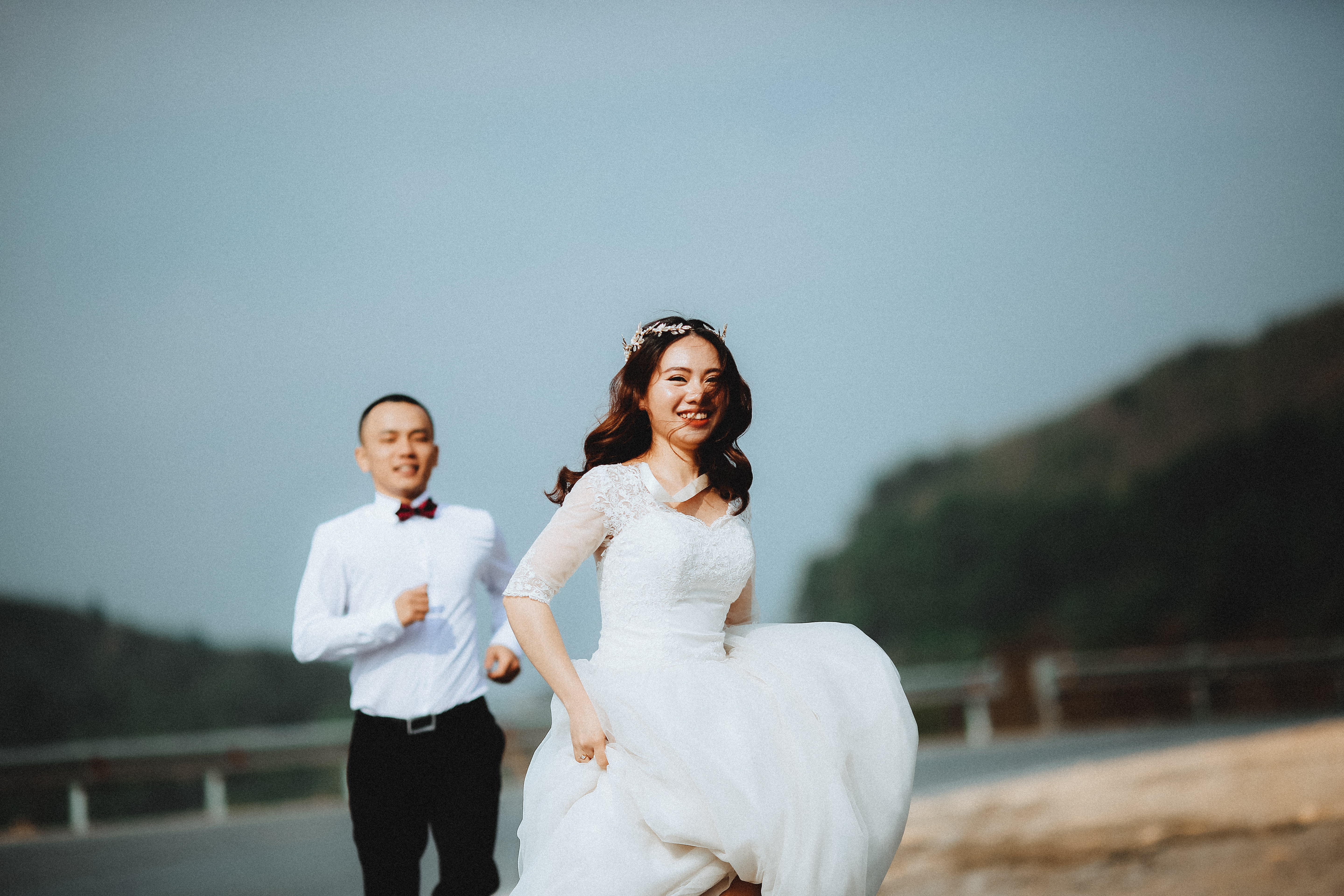 Groom chases after laughing bride in Vietnam with hills behind them