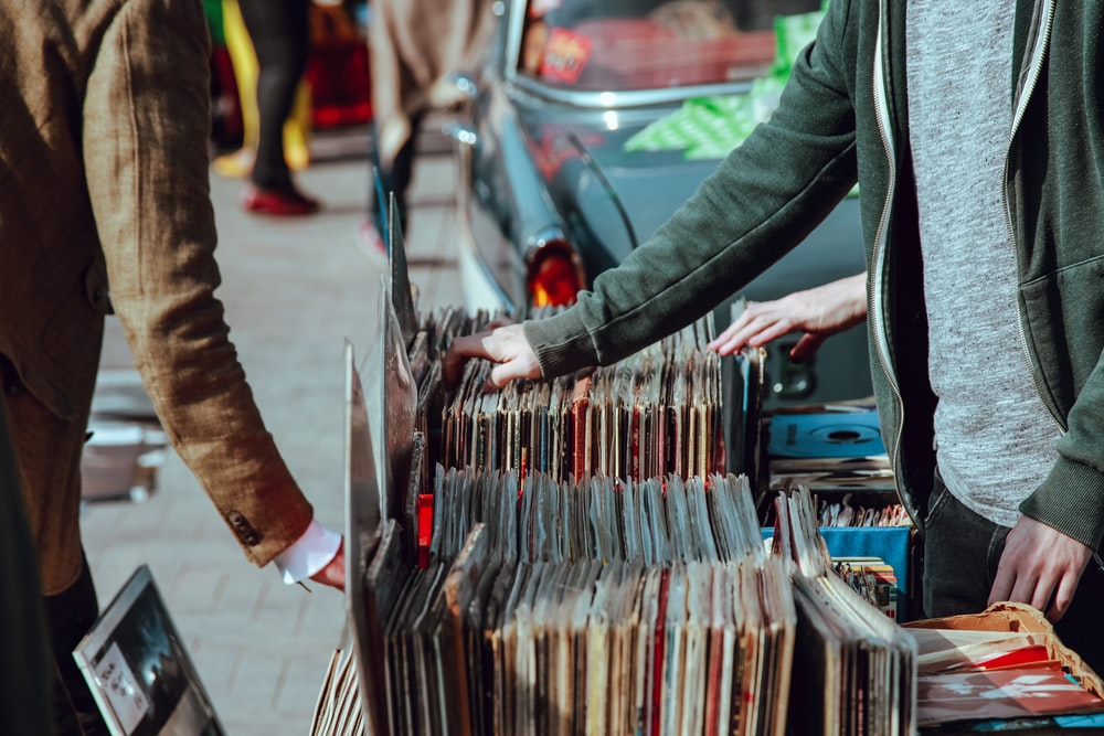 People browsing vinyl records at a stall on the street