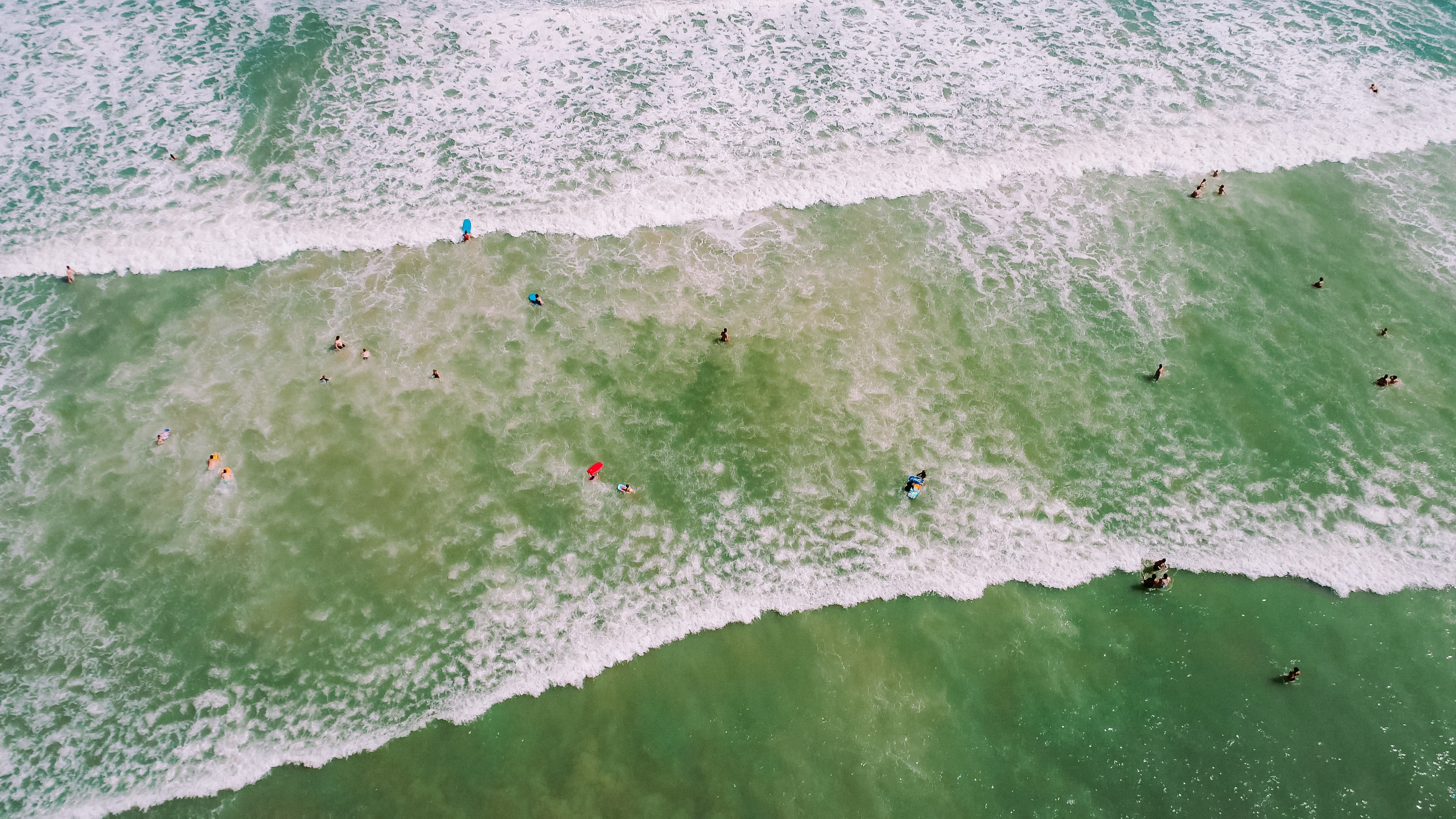 Drone aerial view of the people washed by the waves in shallow water at Cocoa Beach