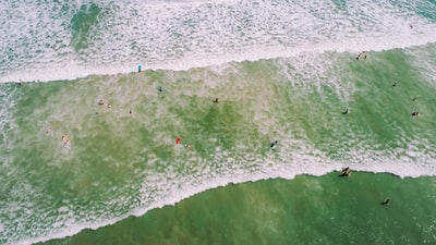 aerial photo of people on seashore with waves and bubbles at daytime drone view teams background