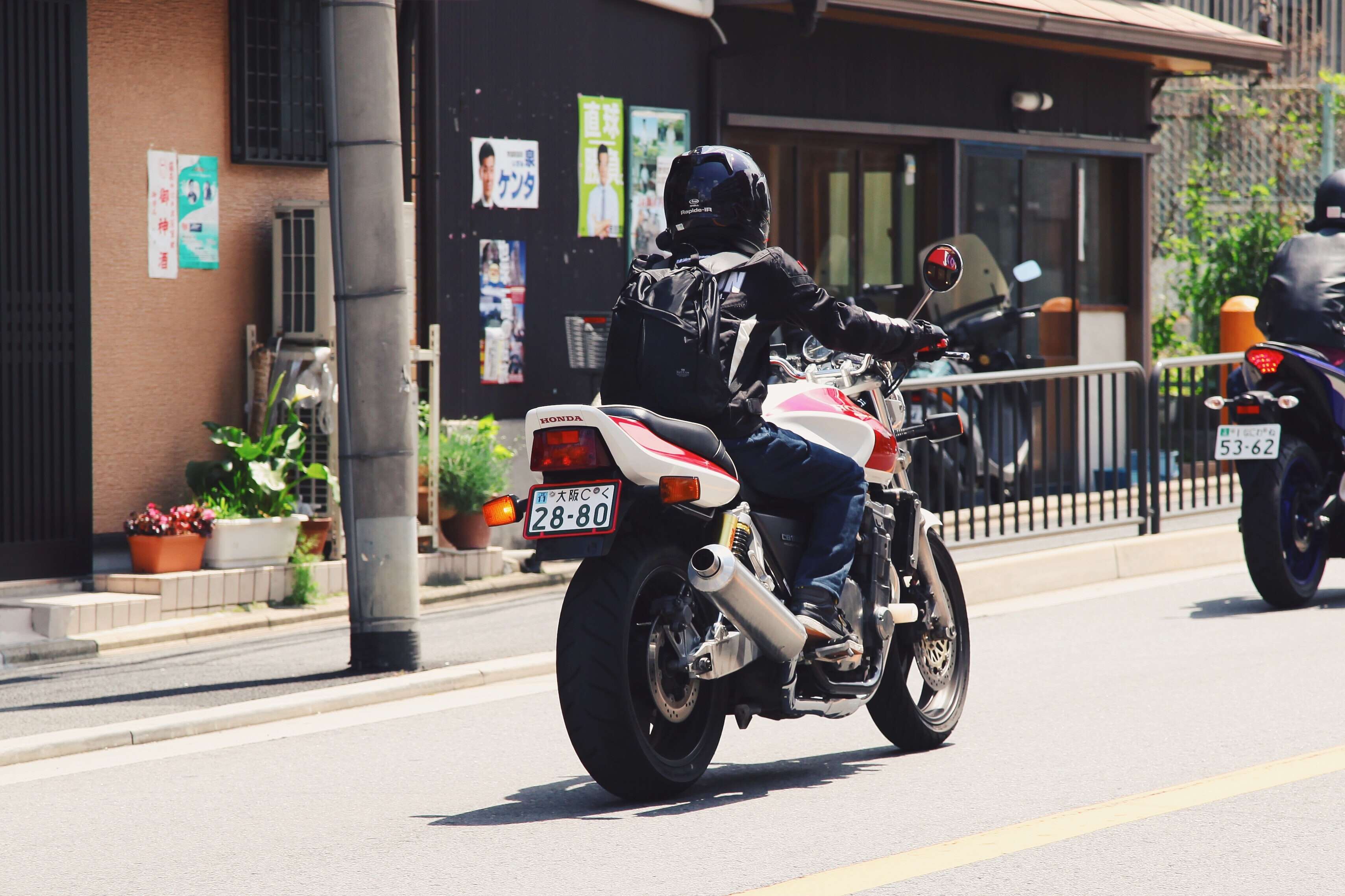A biker in dark clothing with a black backpack driving a motorcycle through a Japanese street with posters in the background