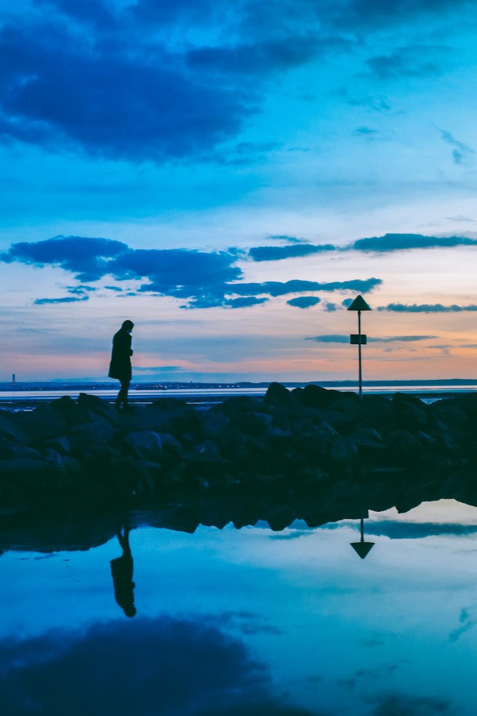 silhouette of person walking on rocks near body of water