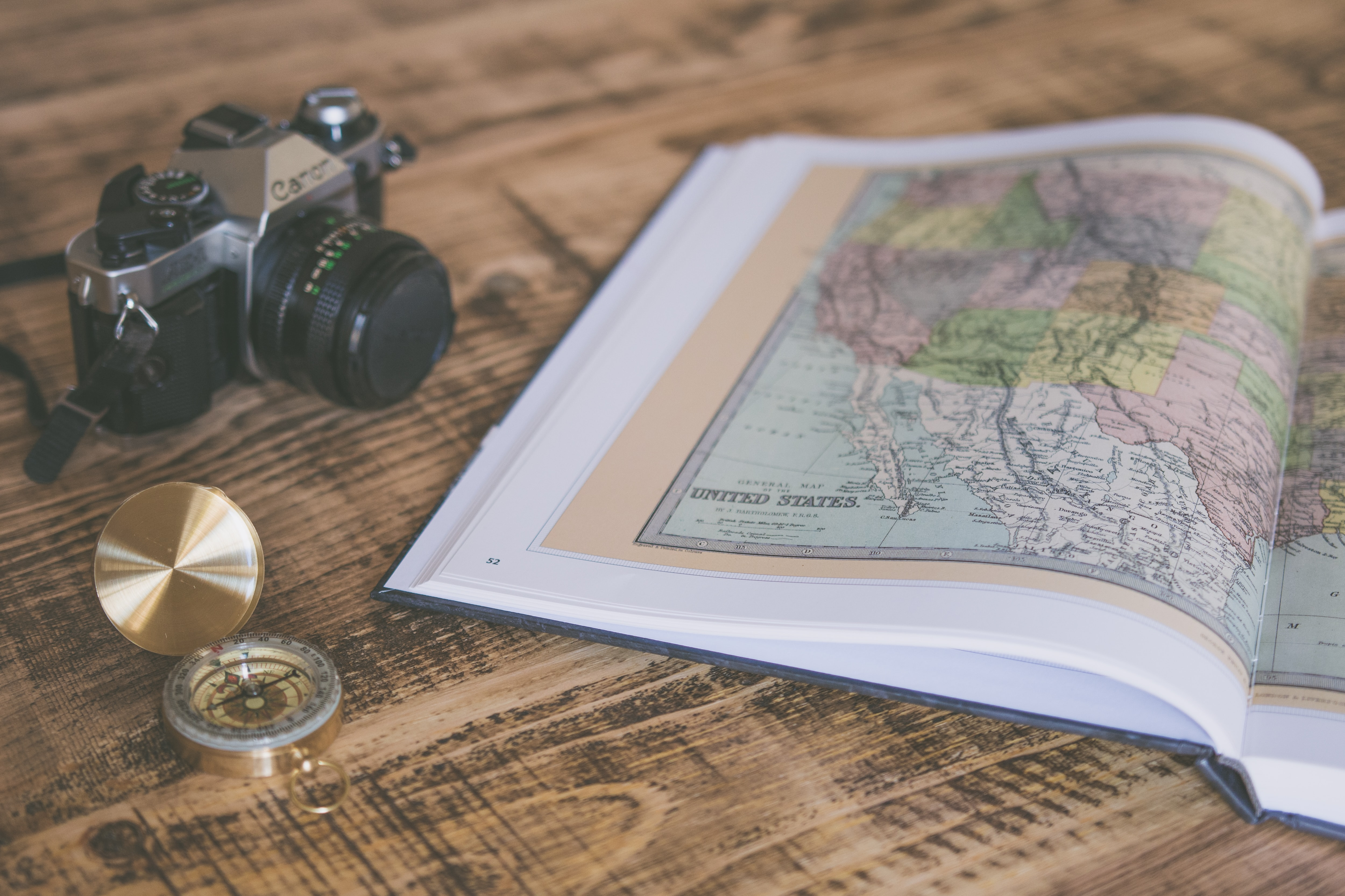 An open atlas with a map of the United States next to a camera and a compass on a wooden surface