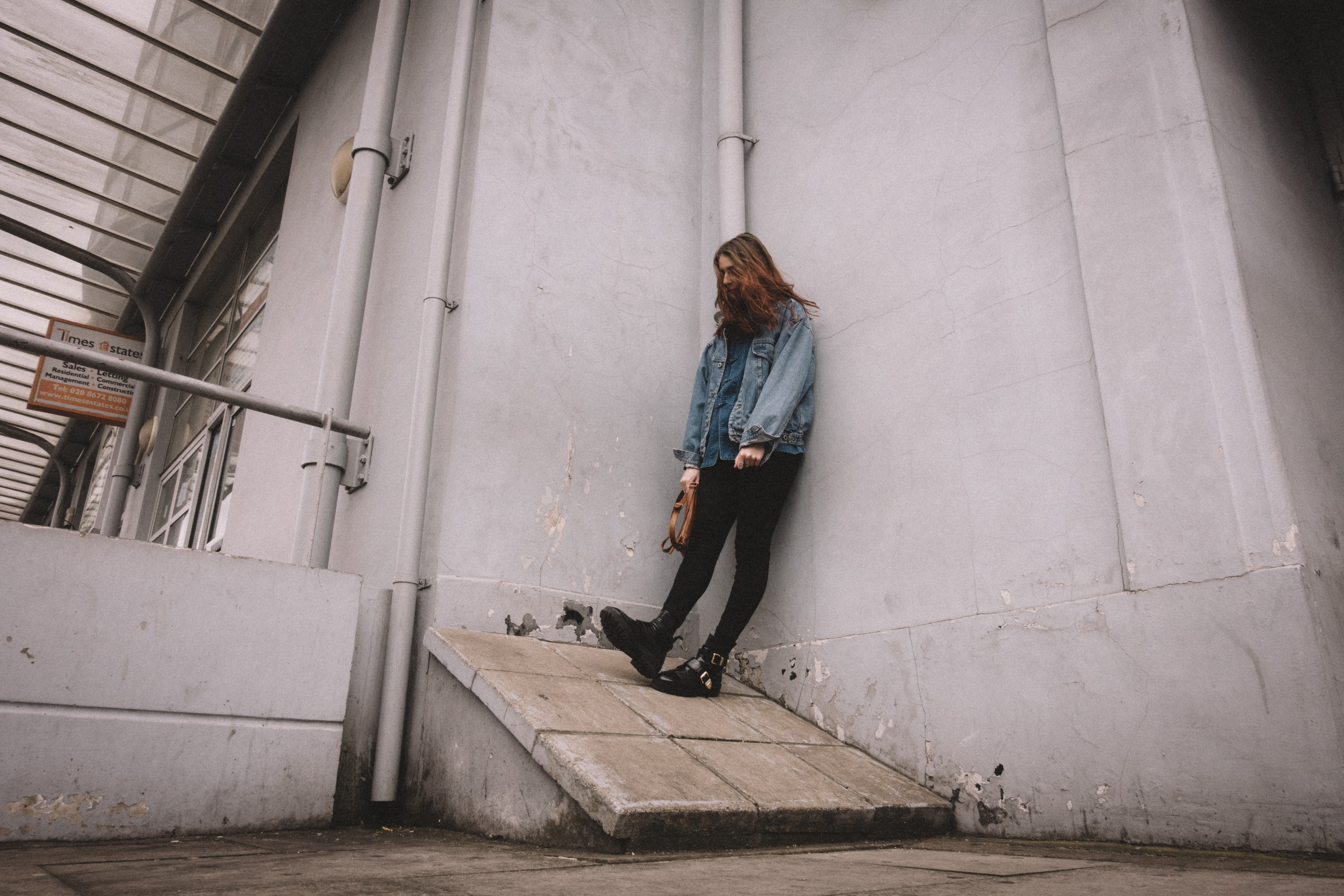 man leaning on gray concrete wall