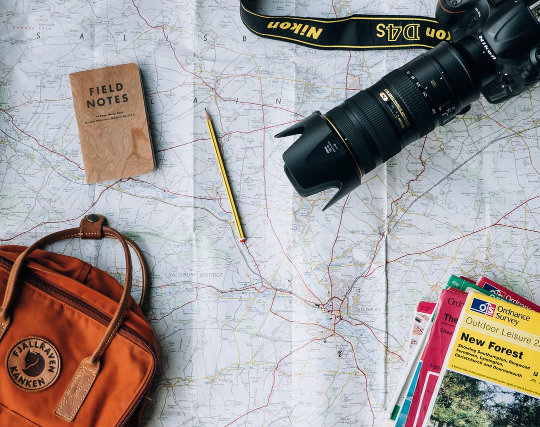 A map that has a field note book, a pencil, a DSLR camera and a backpack laid out on it to signify going traveling.