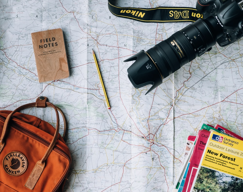 An overhead shot of a long-lens camera, a Field Notes Notebook, a pencil and a travel bag laid out on a map