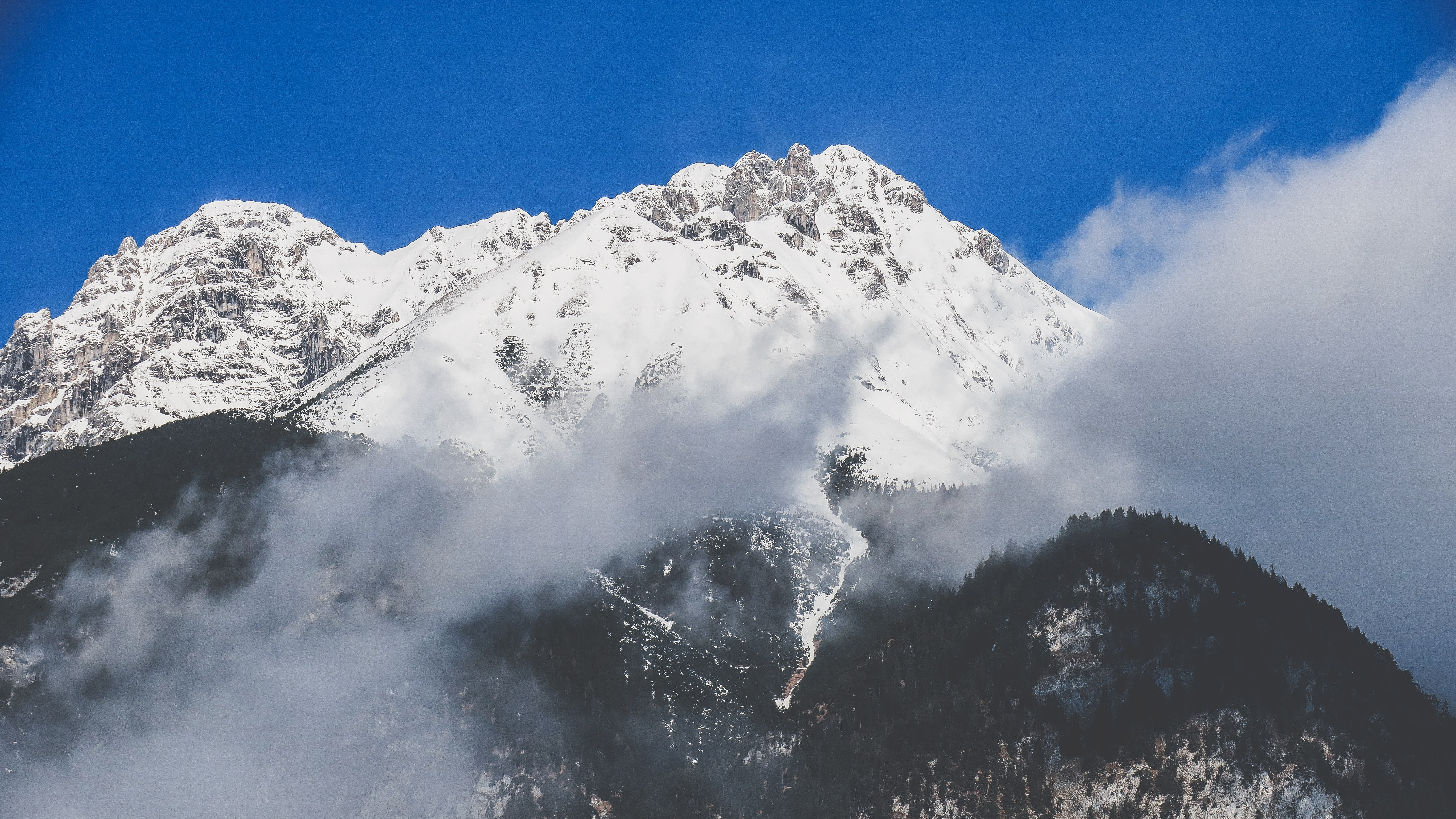 snowy mountain covered by clouds during daytime