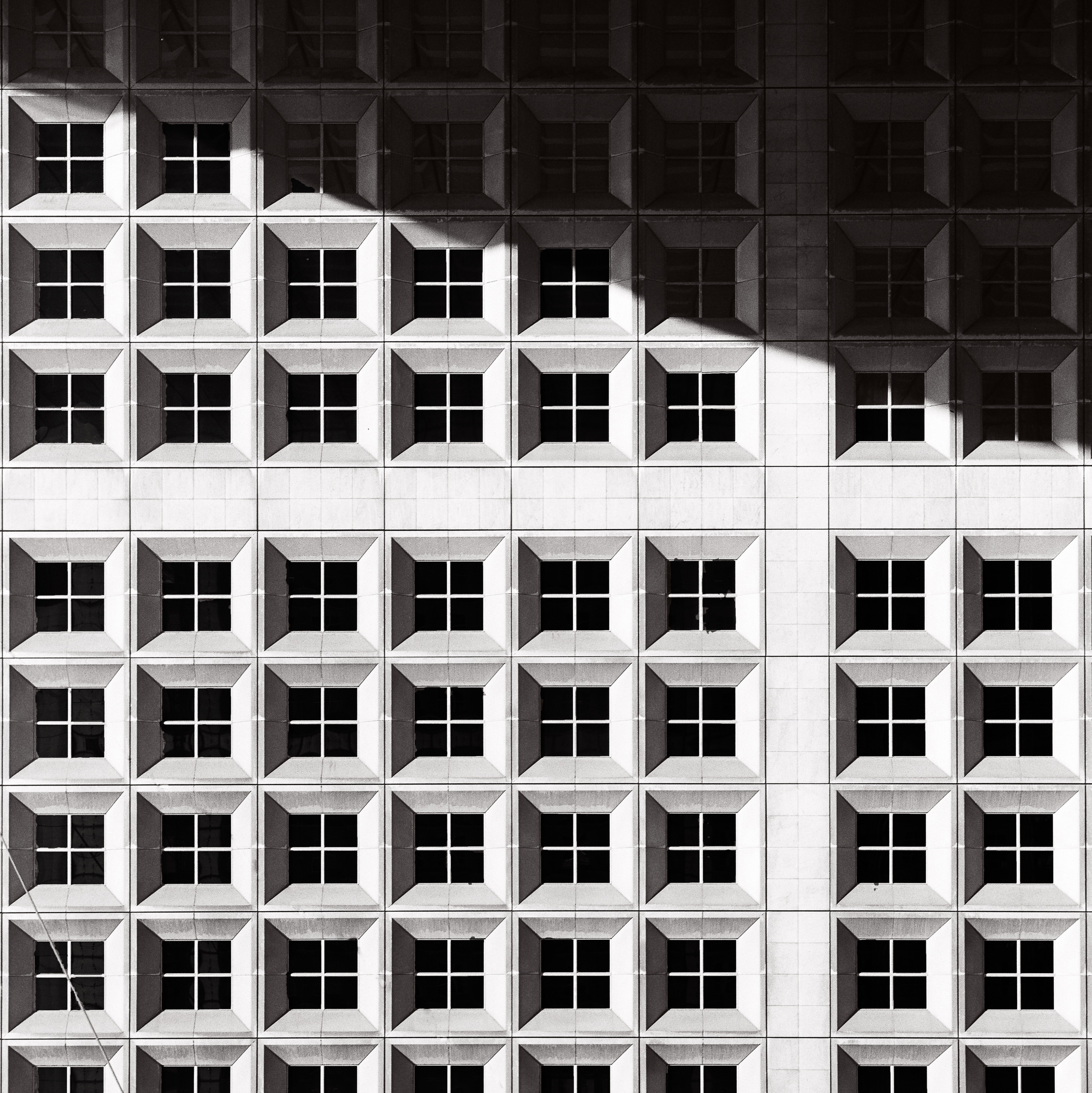 Black and white shot of urban building windows with shadow, Grande Arche de la Defense