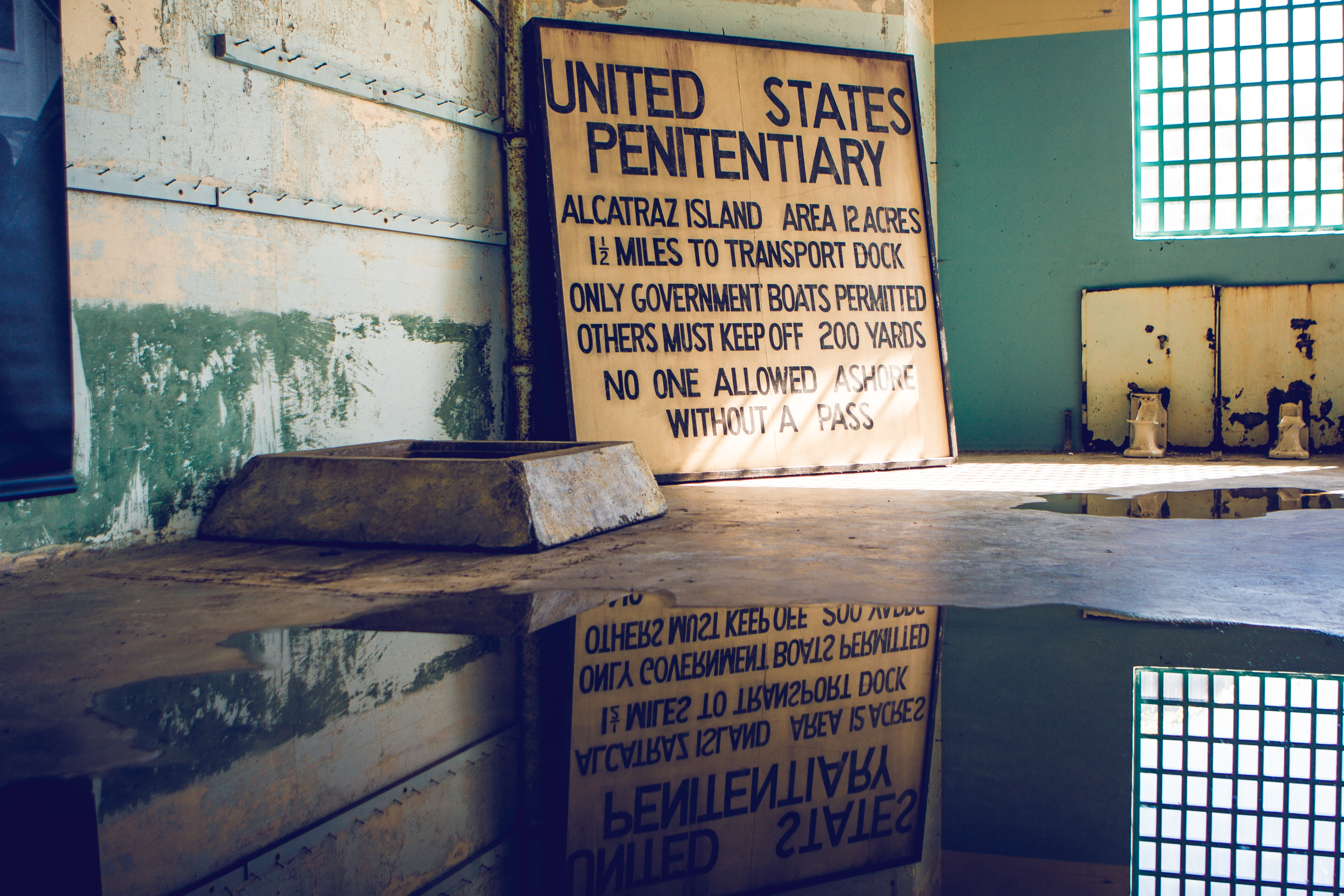 Puddle in an abandoned jail cell reflects old yellow sign for the United States Penitentiary.