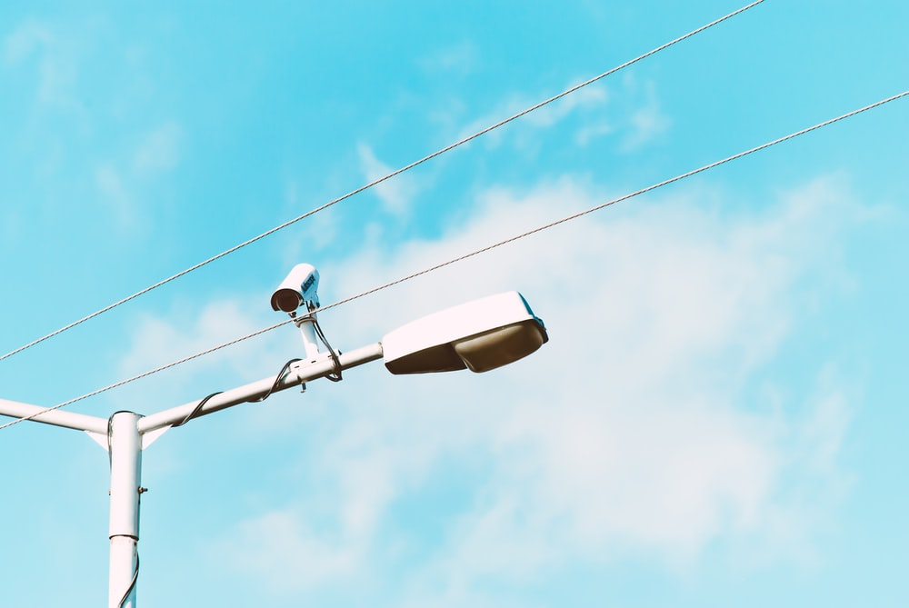 closeup photo of white lamp post and camera