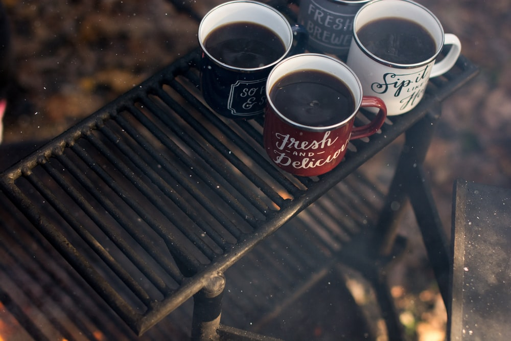 four assorted-color ceramic mugs on black grill frame