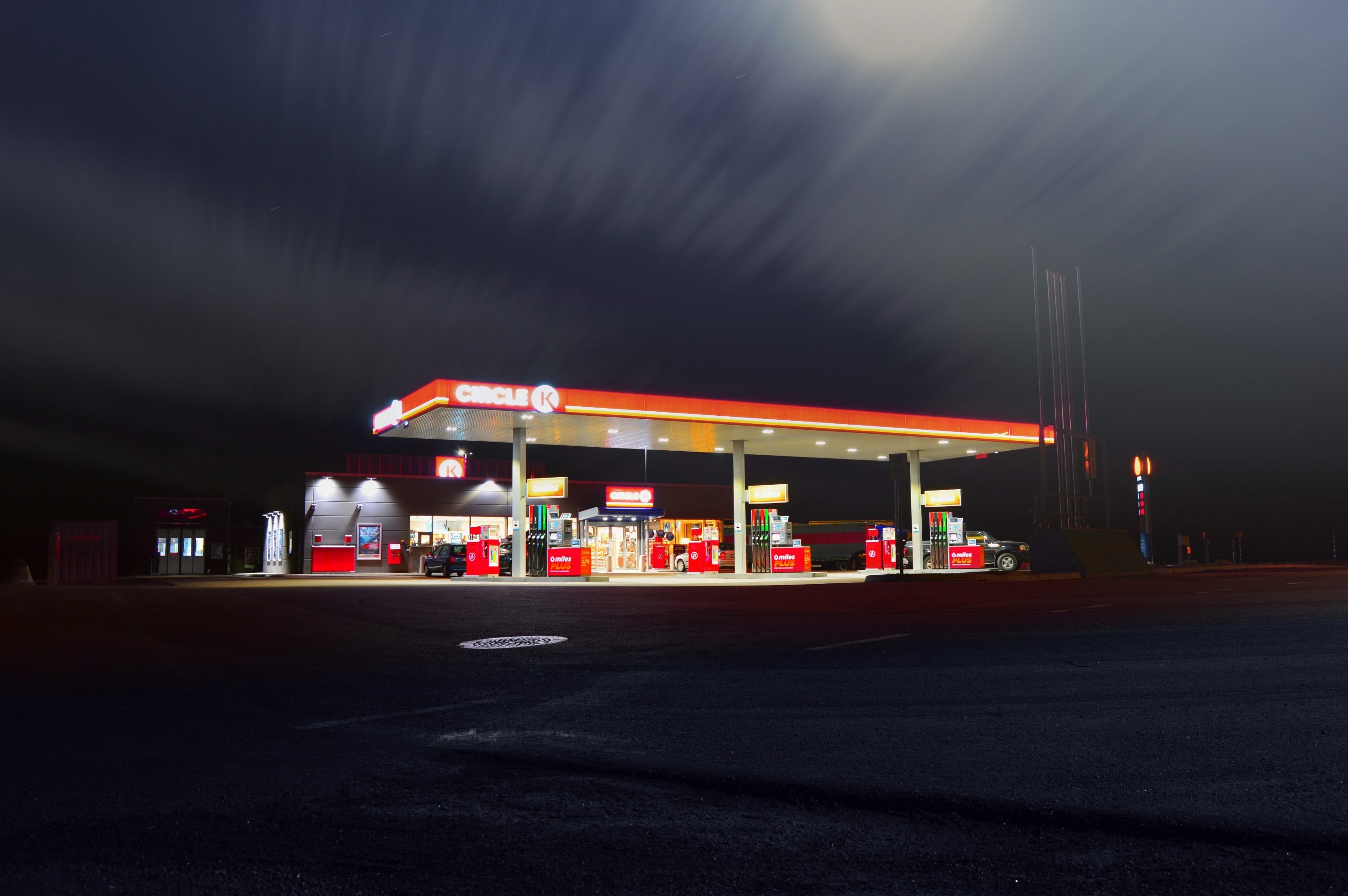 An overexposed gas station illuminated with a blurry night sky above