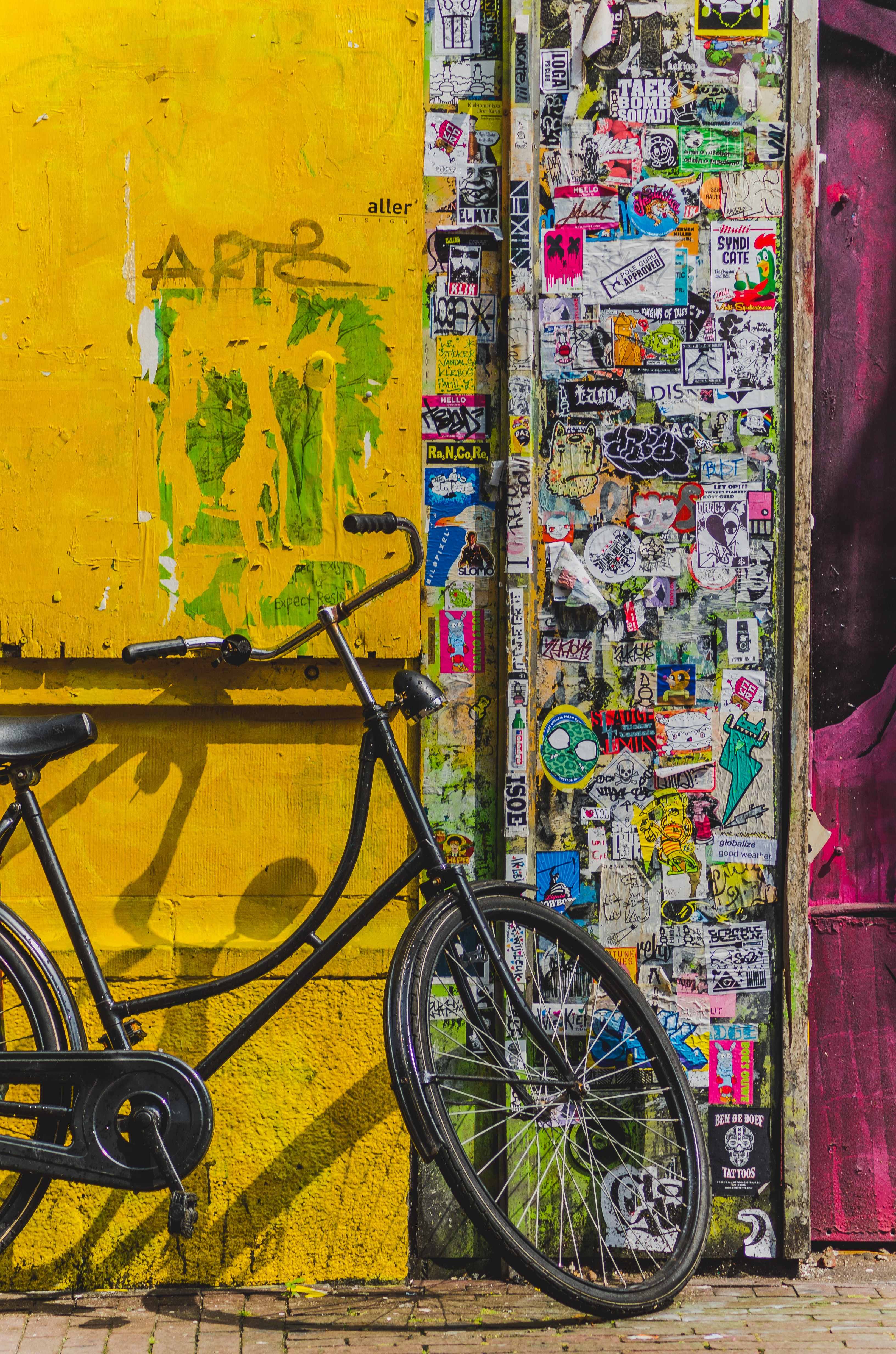 bike parked beside wall full of stickers