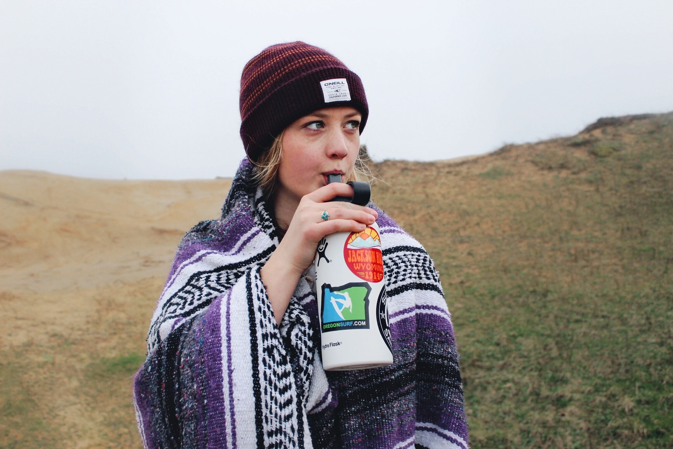 A woman in a knit cap and blanket drinks from a water bottle at Cape Kiwanda