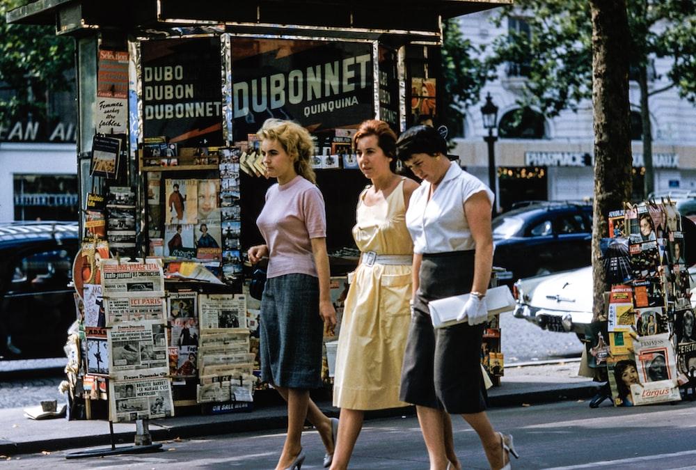 three women walking on road