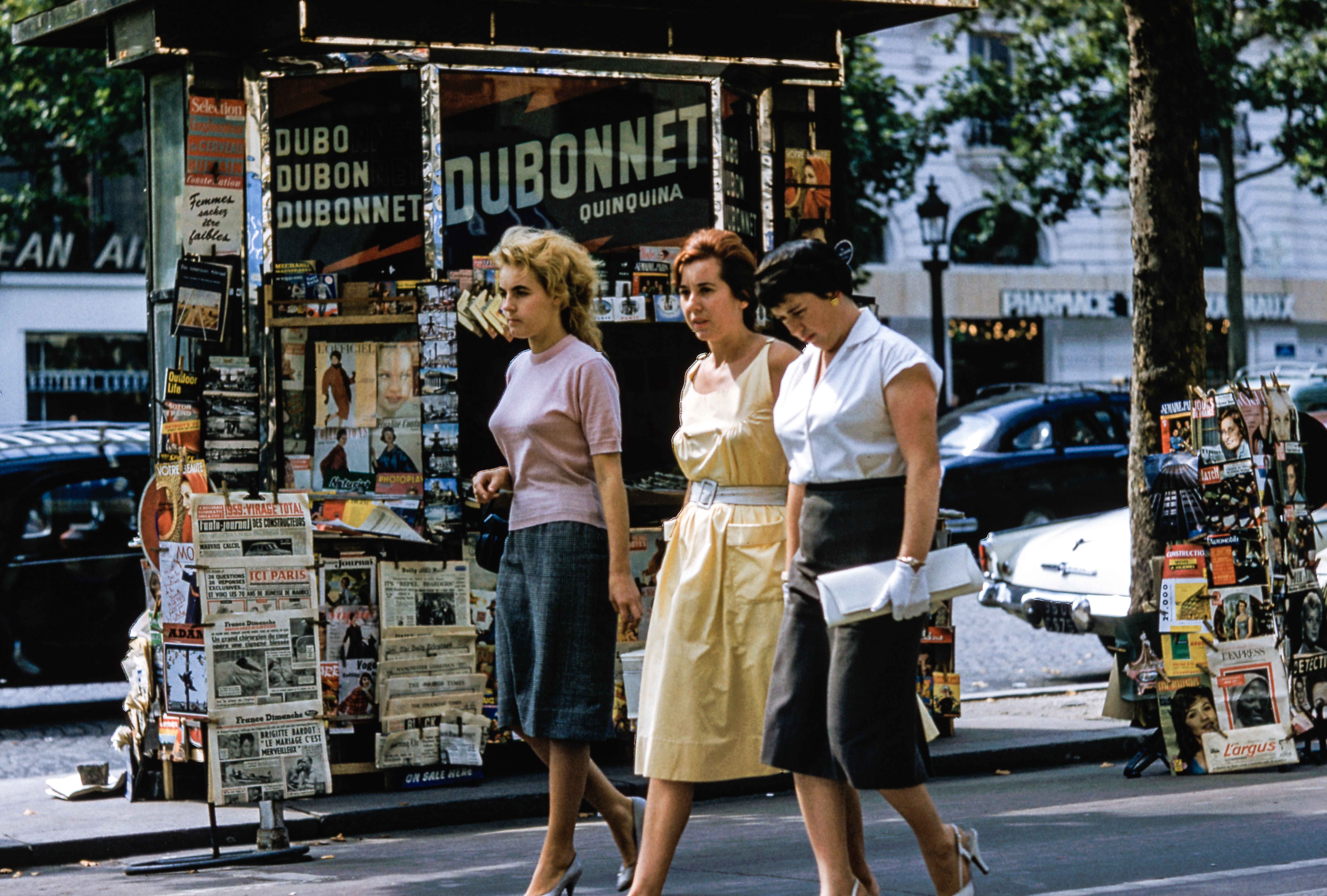 Three women in retro clothes walk on the sidewalk by a news stand