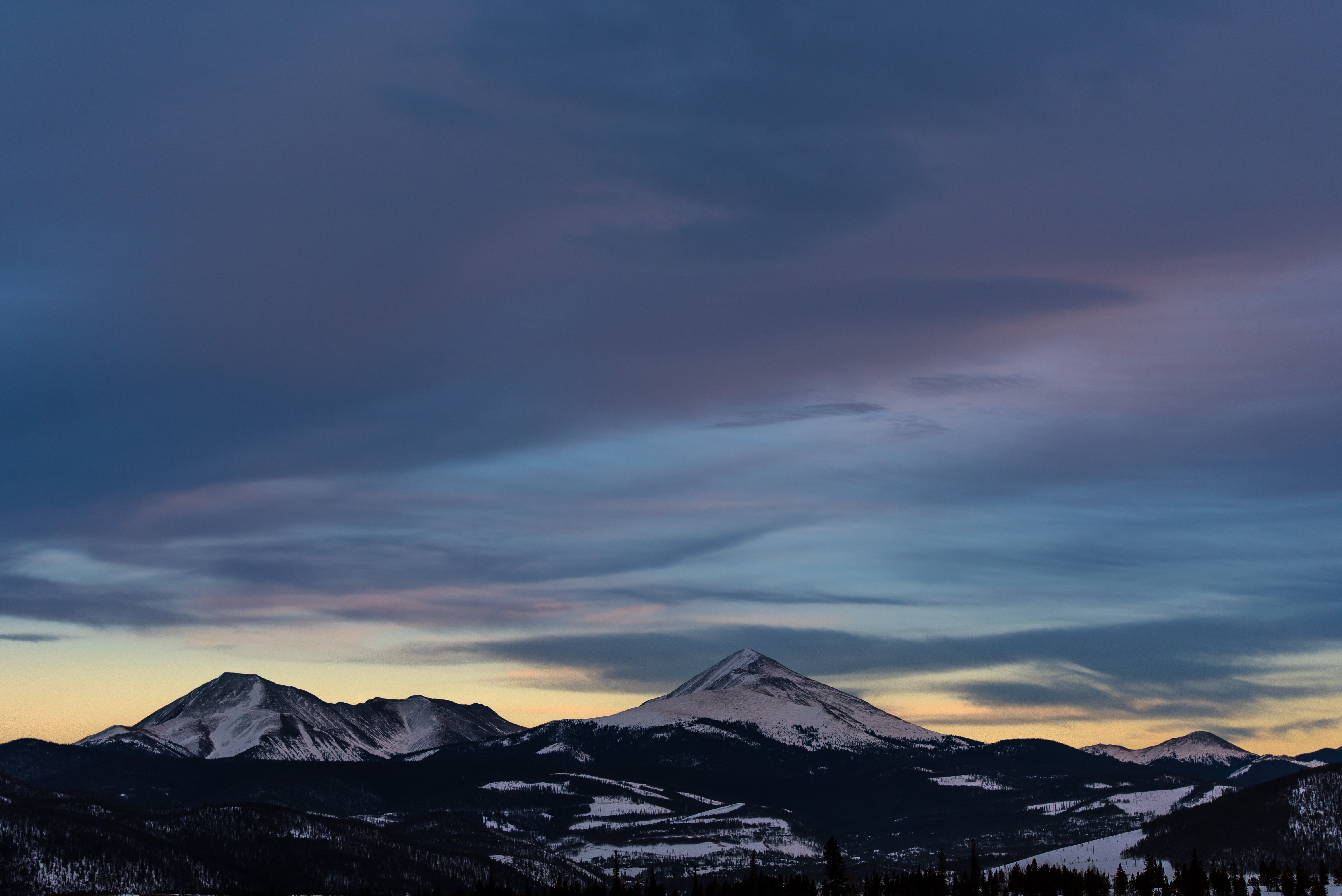 Dark evening clouds over snow-capped mountain peaks in Silverthorne