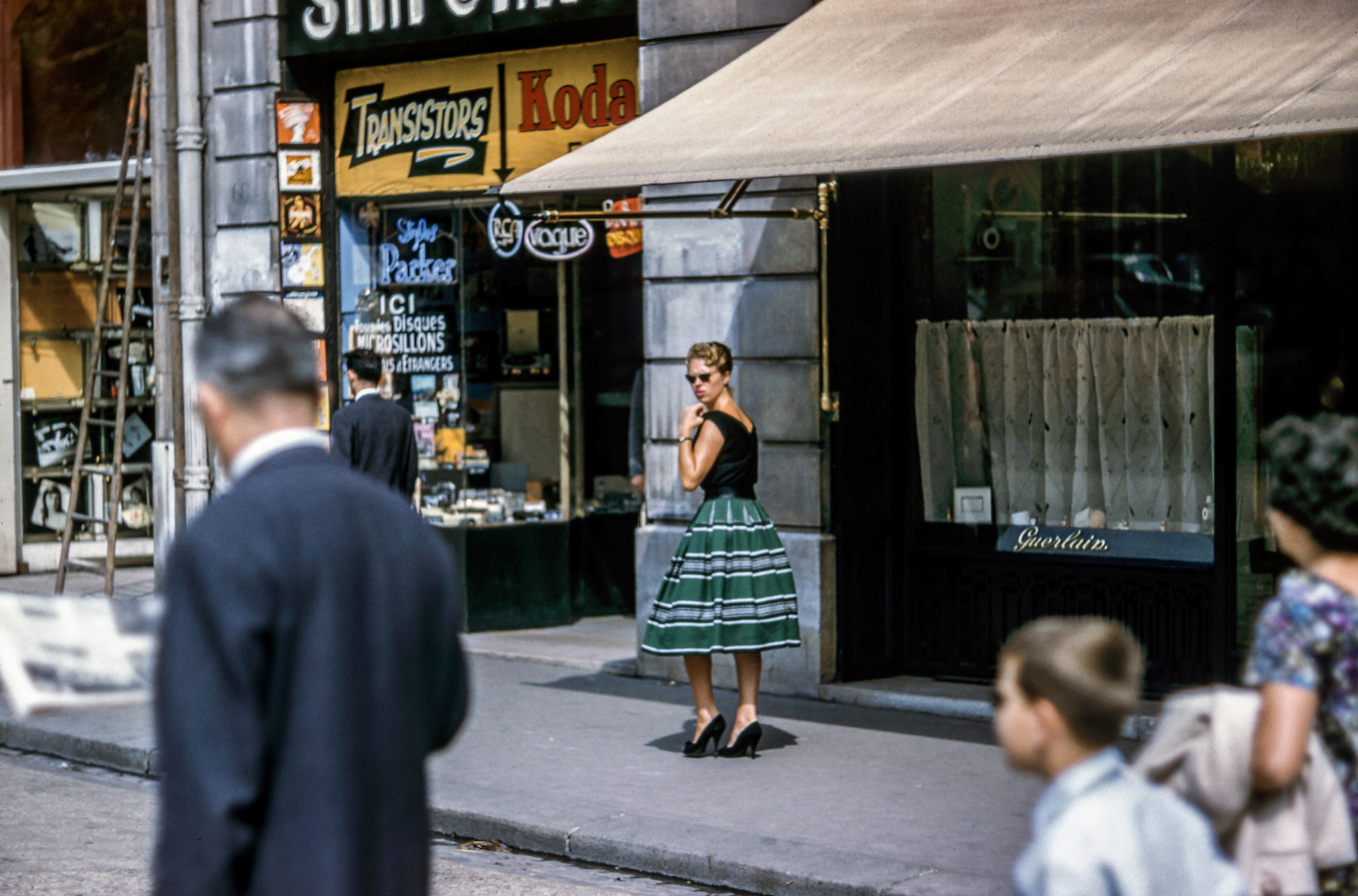 A woman in a green skirt in a French street looking back