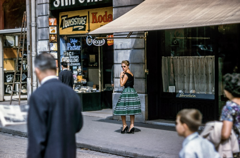 woman looking left while standing beside store along the road