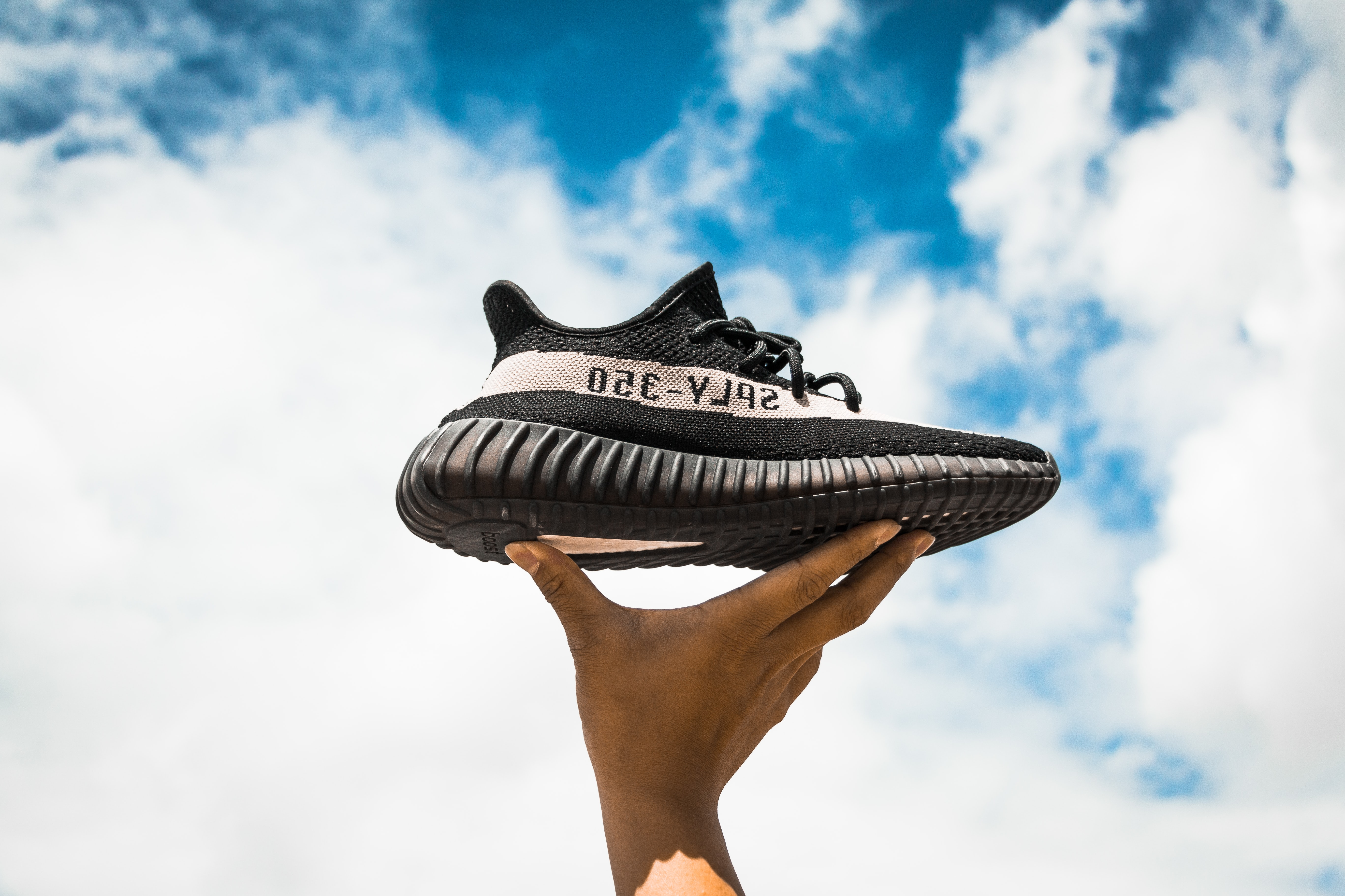 unpaired adidas Yeezy Boost 350 V2 shoe on person's hand