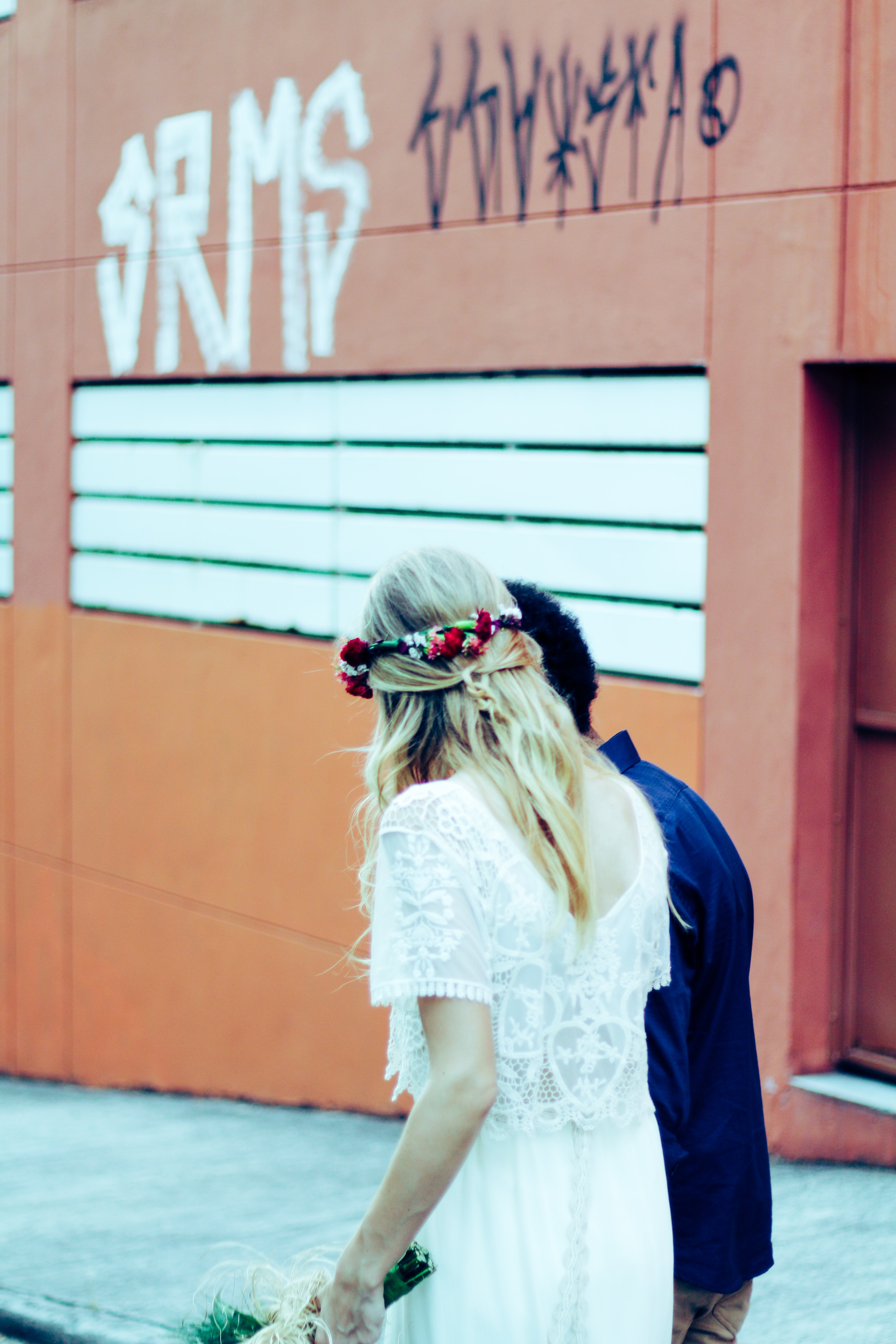 Wedding couple walks down street in Santo André with graffiti on building