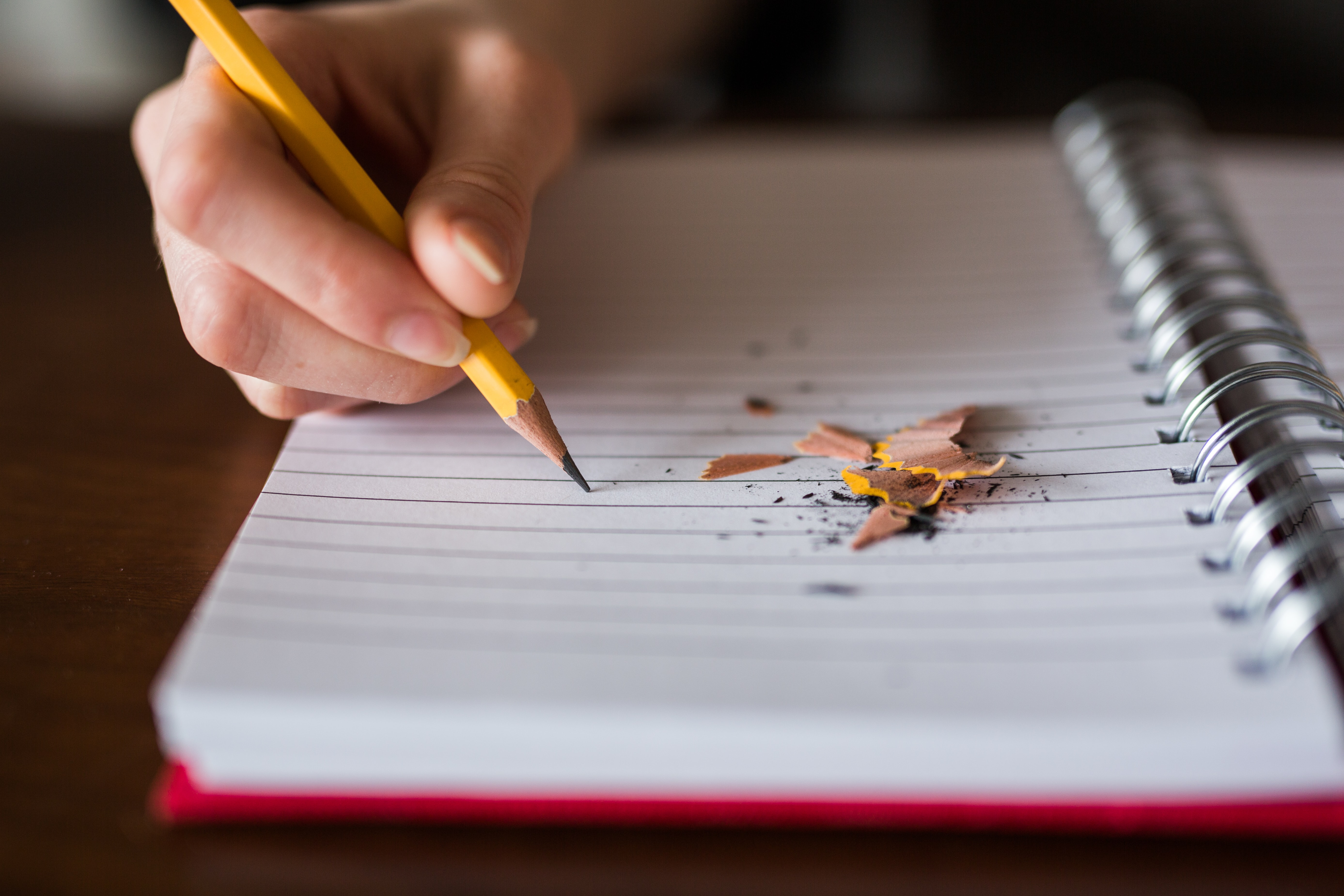 A person writing with a pencil in a notebook with pencil shavings on it