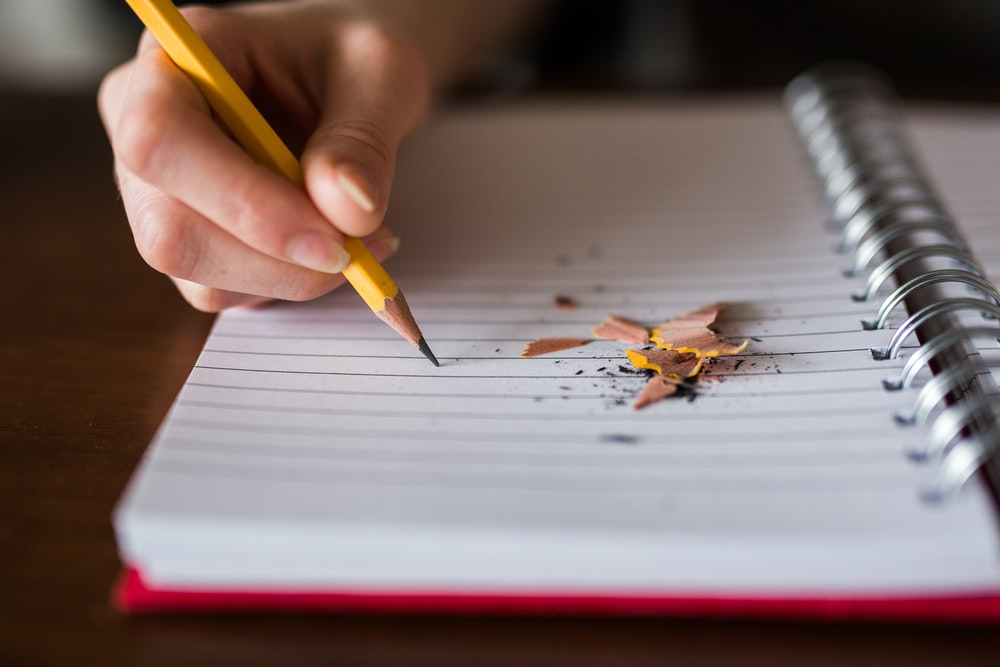person holding pencil writing on notebook