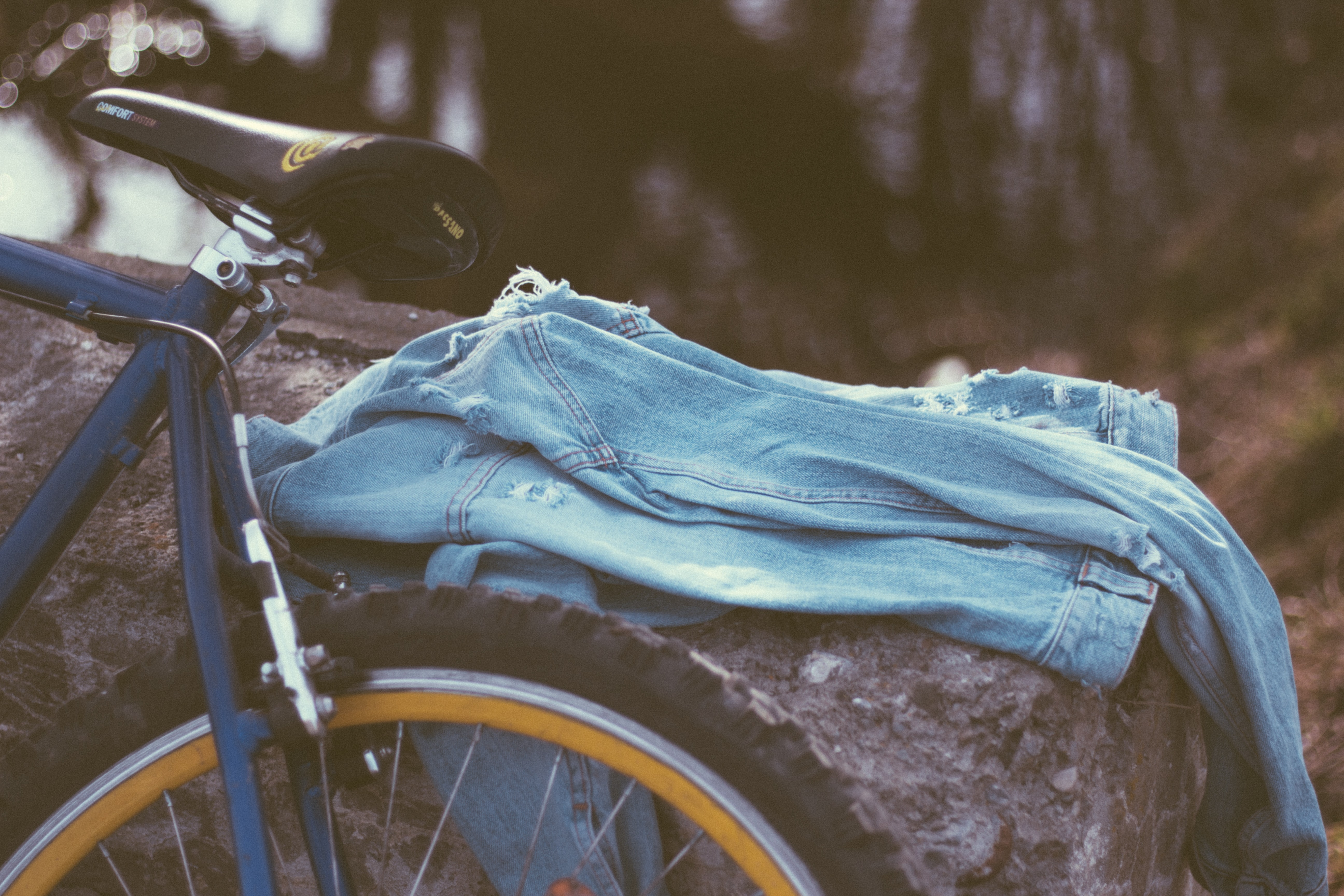 A pair of blue denim jeans on a log next to a bike in Prejmer