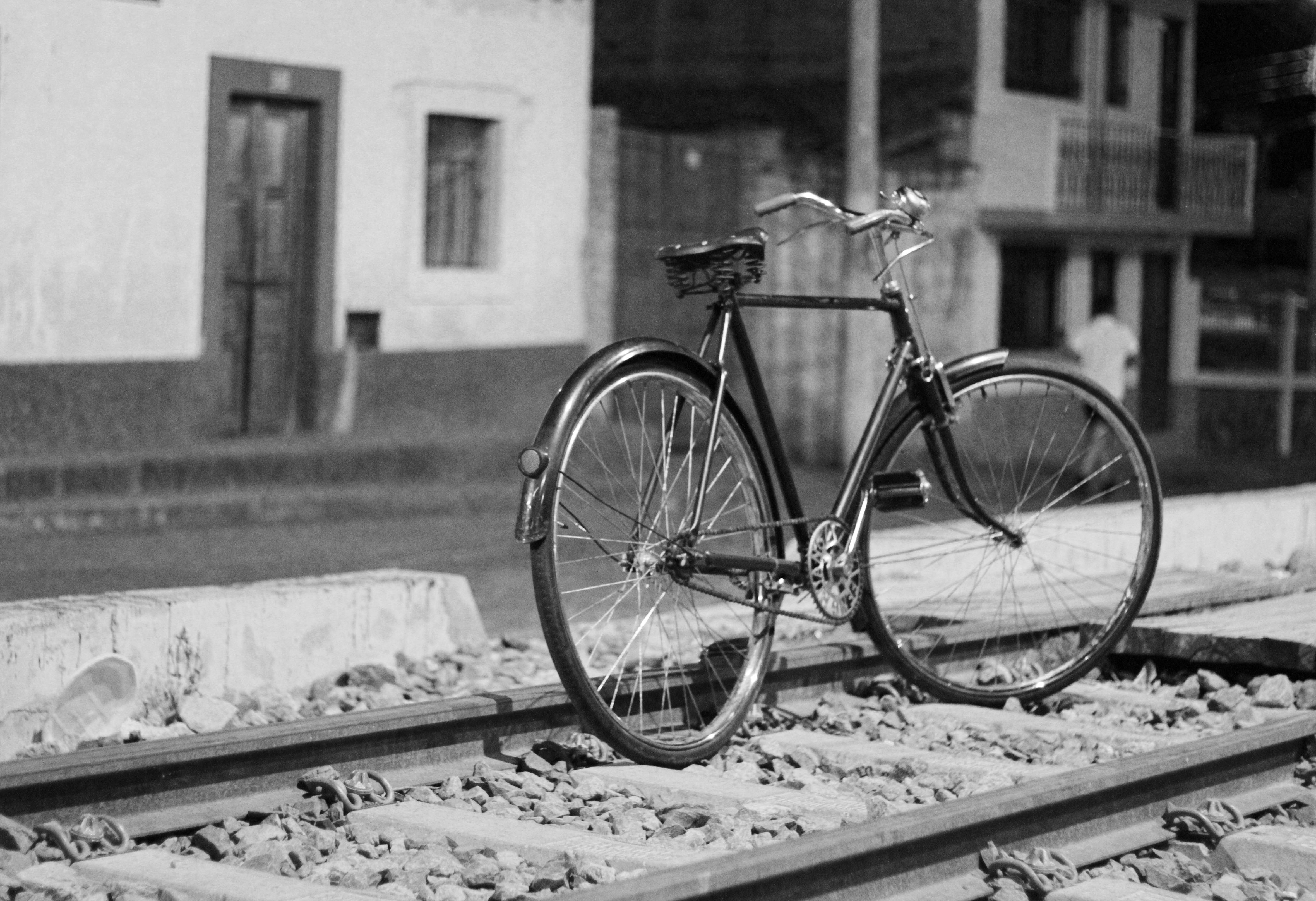 Black and white shot of lone bike standing on railroad tracks with building in background