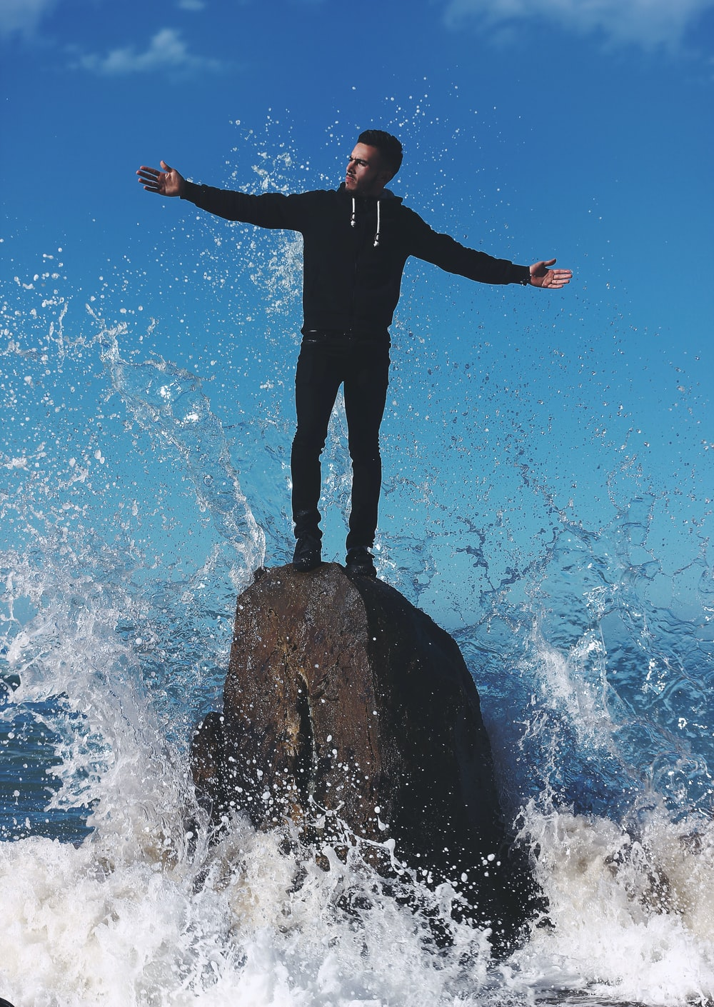 man standing on rock surrounded by water