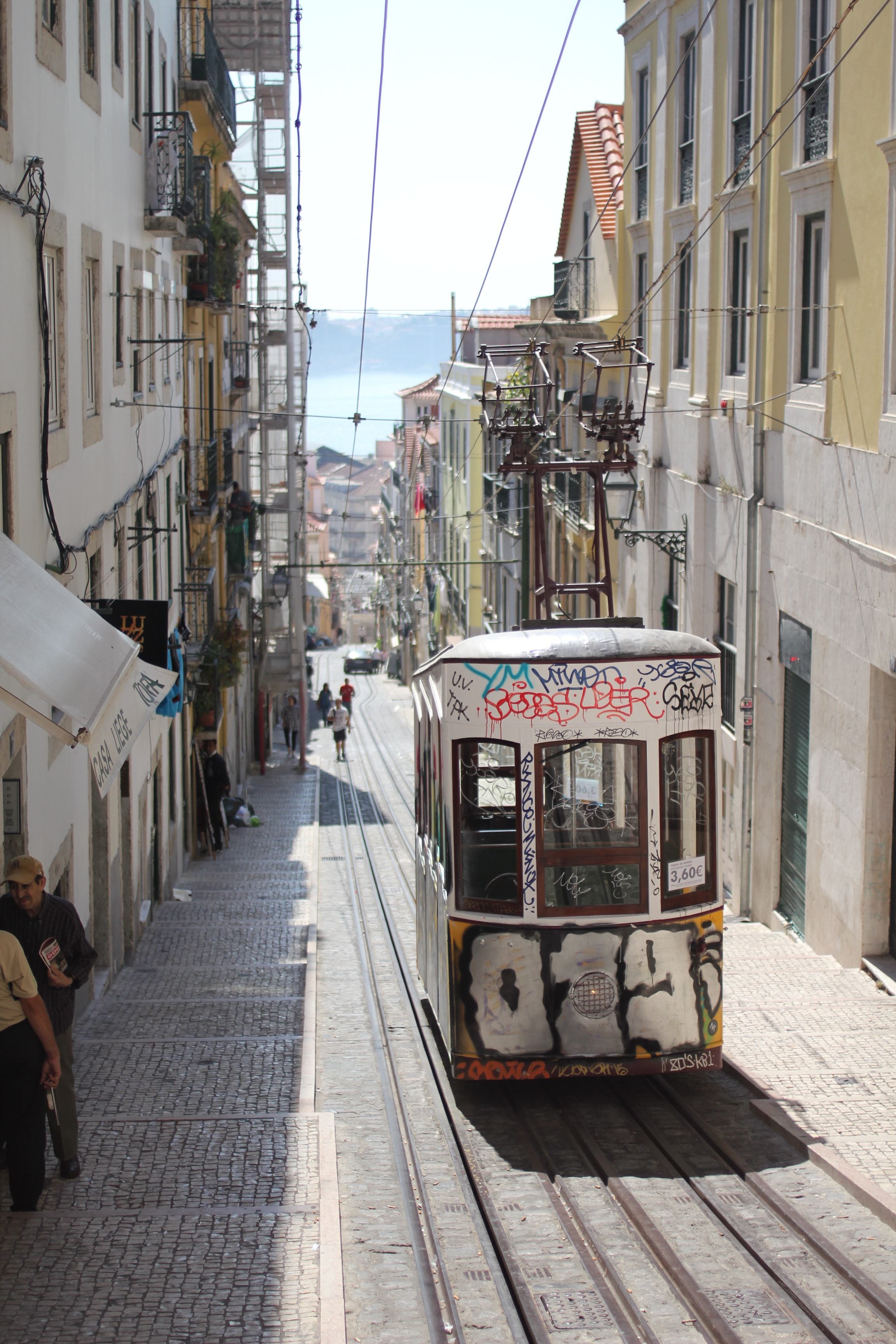 Abandoned street tram filled with graffiti sitting stationary in a Lisbon street as people walk by