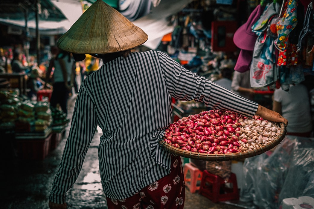woman carrying a basket of vegetables through a busy market