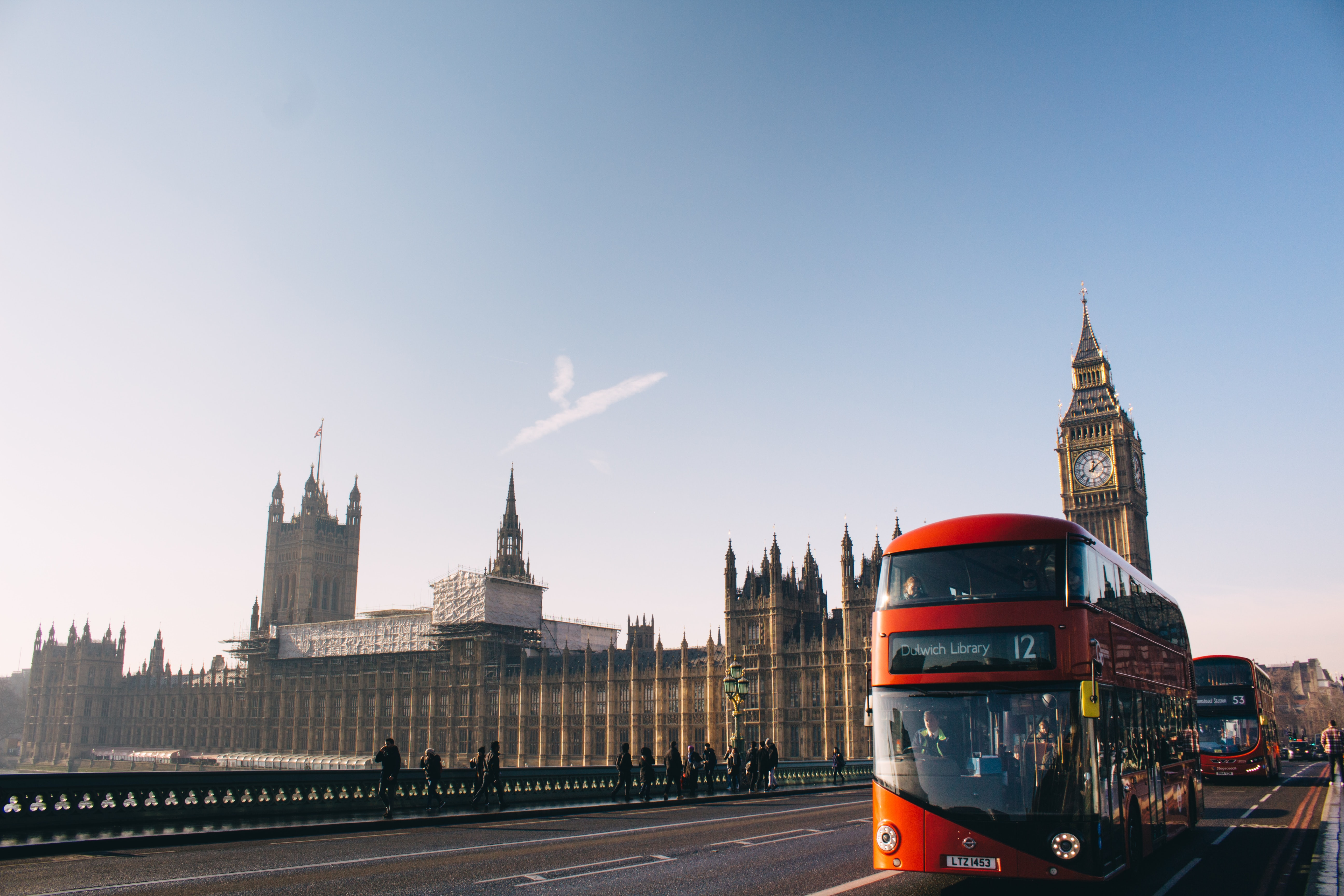 Red double-decker buses on a bridge in London with a view on Westminster
