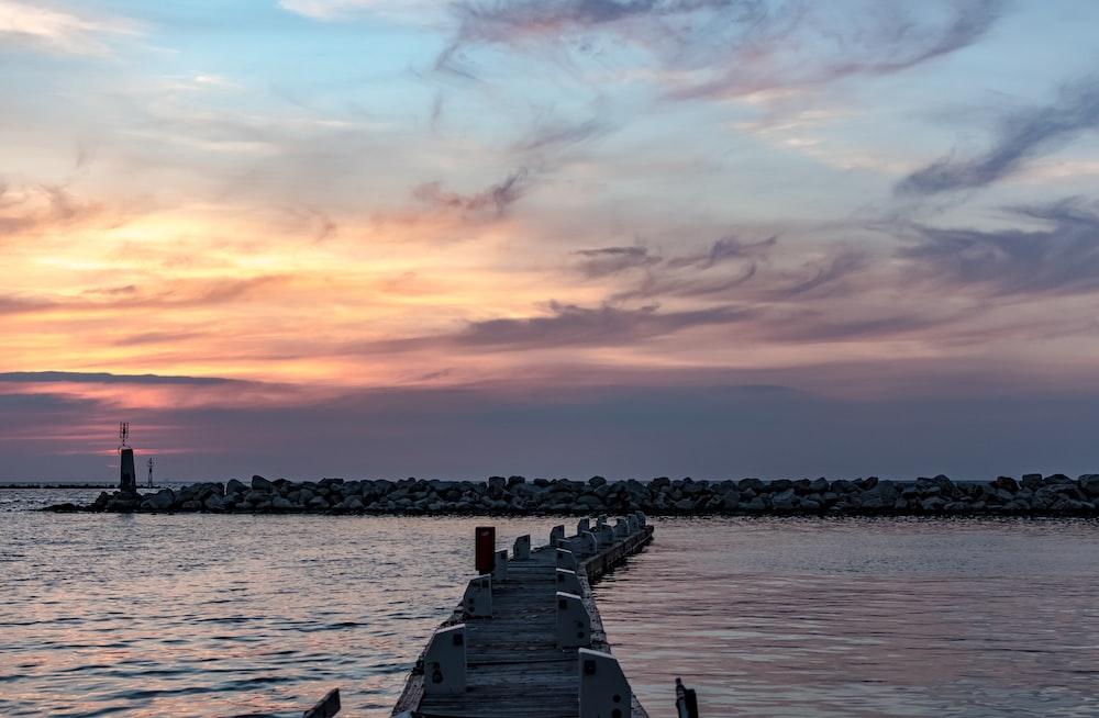 brown wooden dock under gray and orange skies