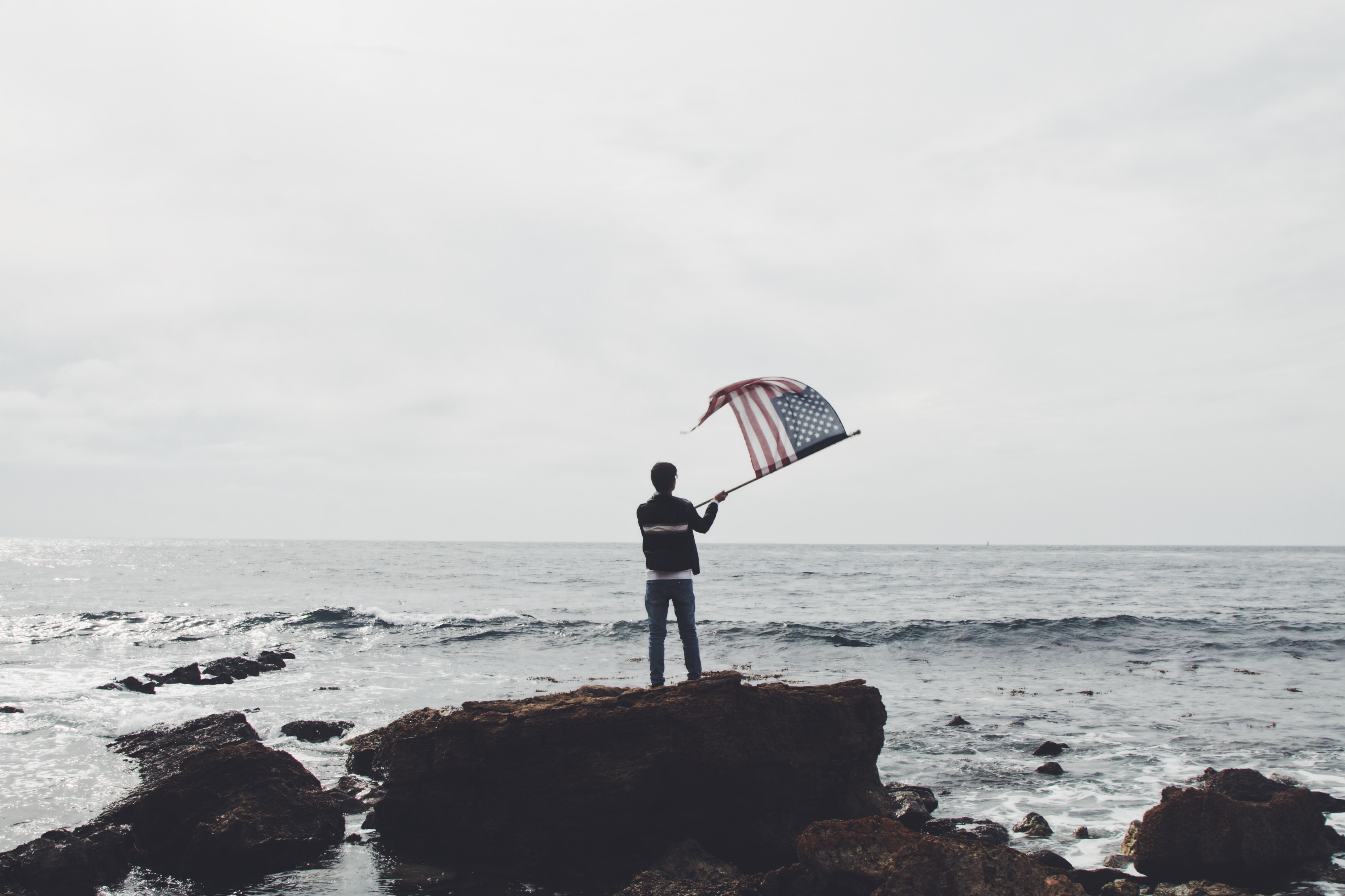 man holding flag of America standing on boulder near seashore