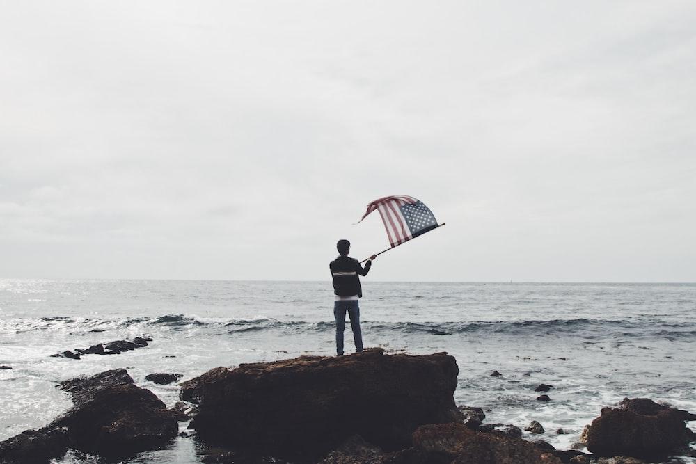 man holding flag of America standing on boulder near seashore