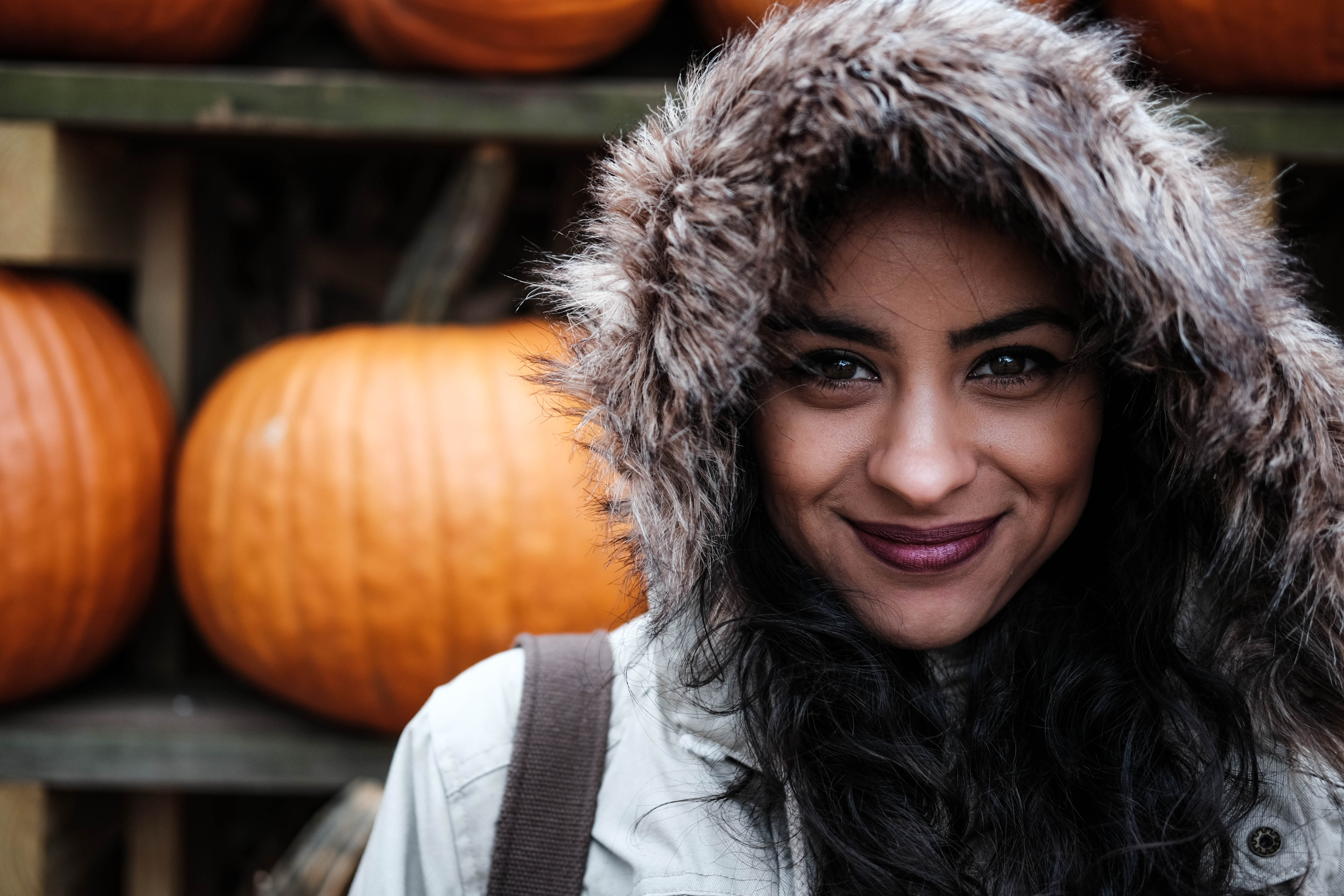 A woman wearing a fur hood and maroon lipstick smiles in front of shelves of pumpkins