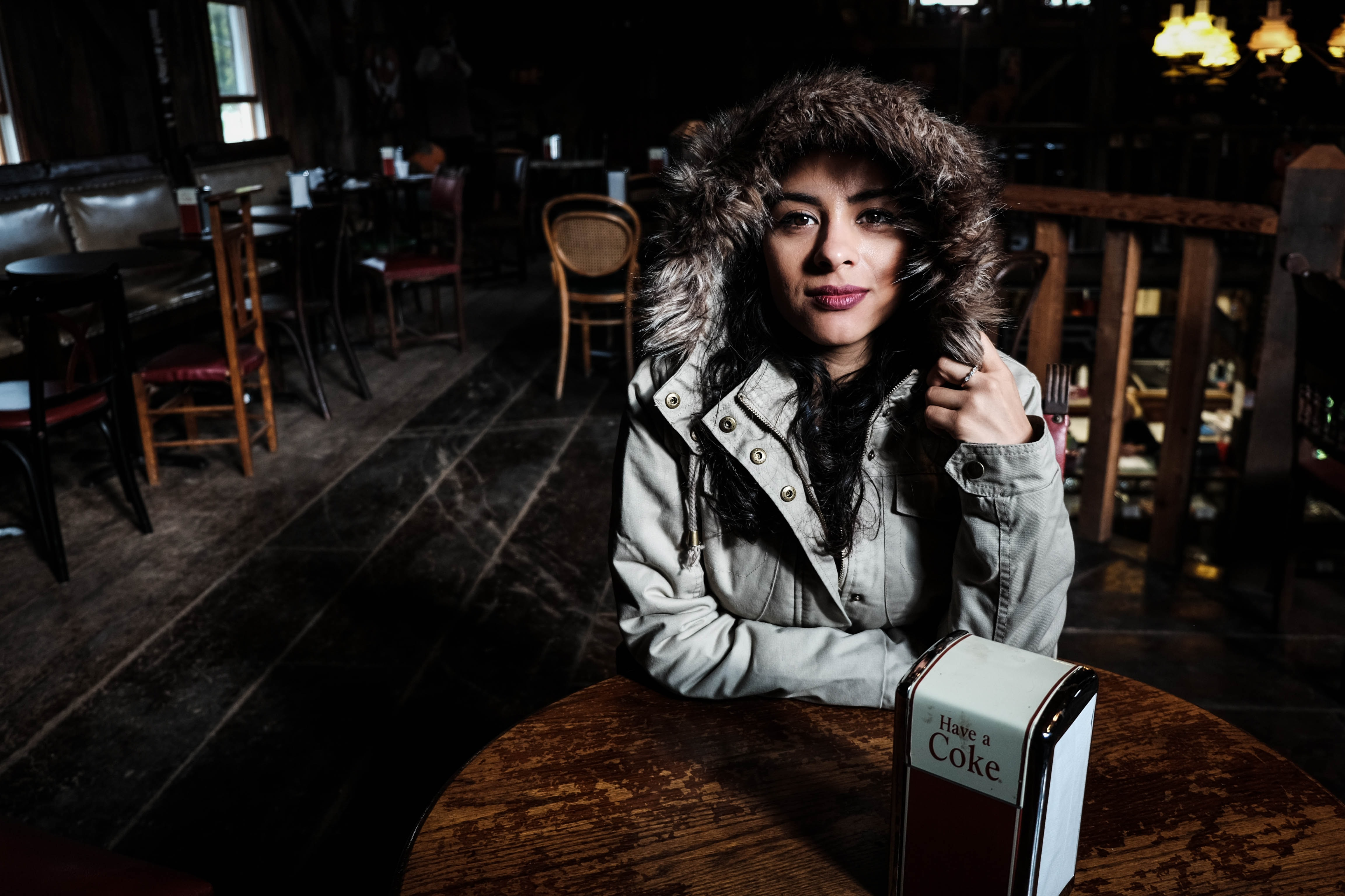 A woman in a fur-lined coat sits in a table at a dark and empty restaurant
