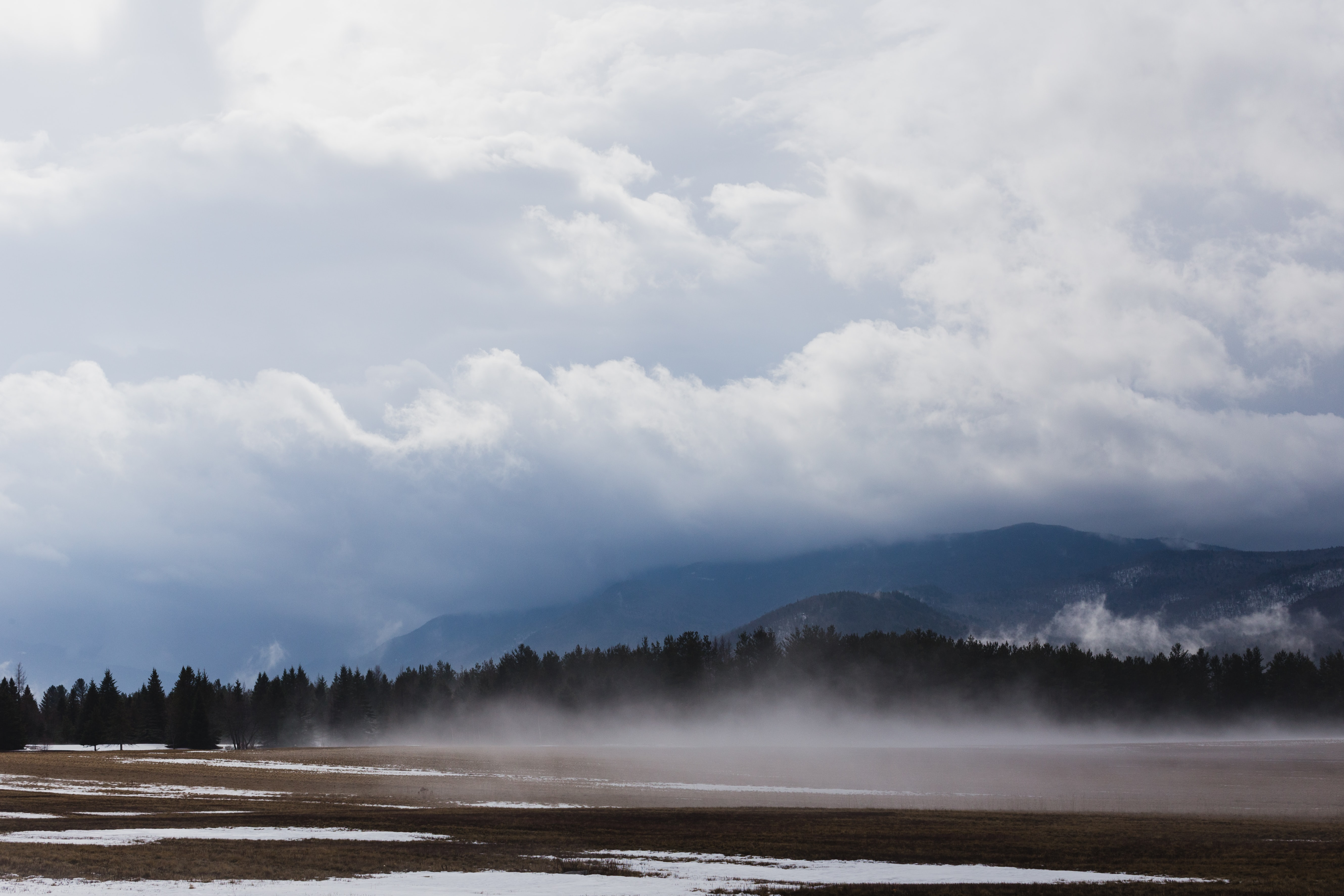 Haze over a field with long patches of snow in Keene Valley
