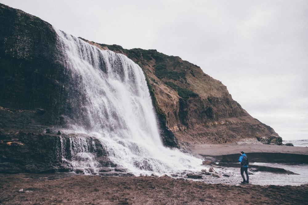 photo of man standing near waterfalls