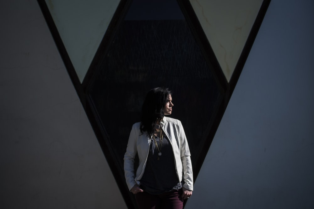 woman standing behind black wall while looking right side