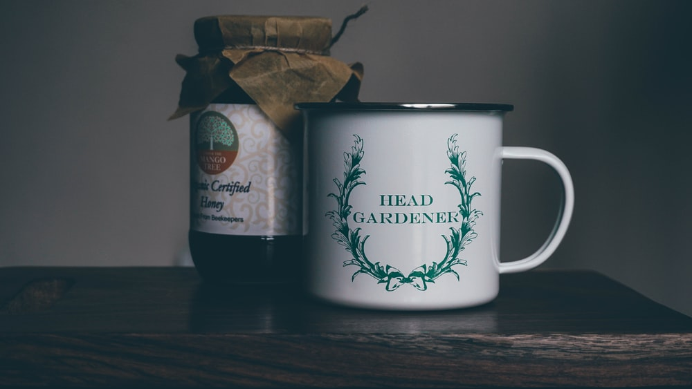 white head gardener ceramic cup near glass jar on brown panel