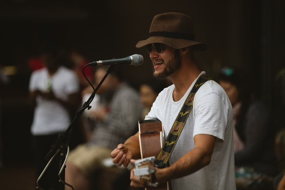 selective focus photography of man playing guitar and using microphone